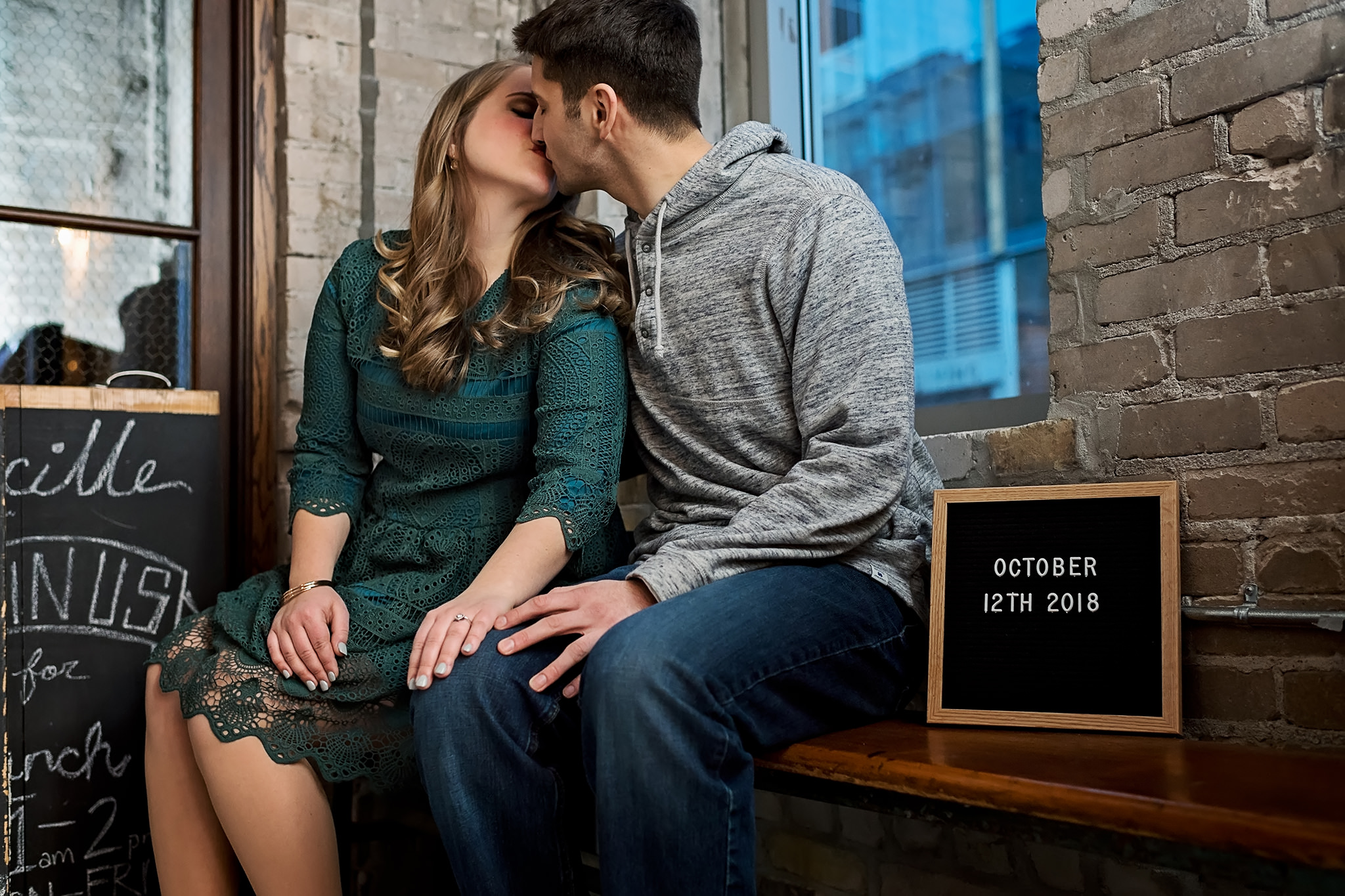 Couple kissing with sign with their wedding date on it