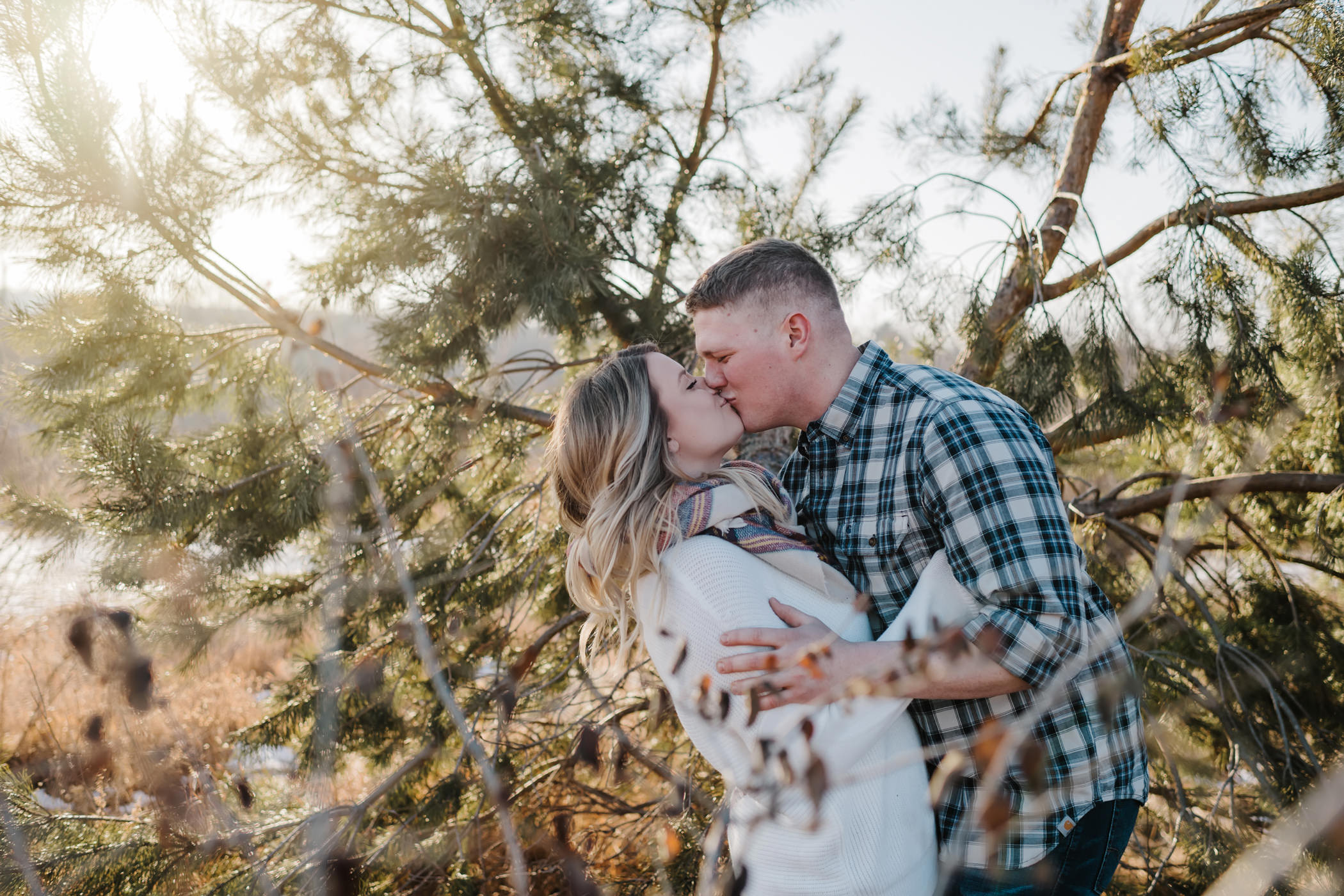 Couple kissing by a tree