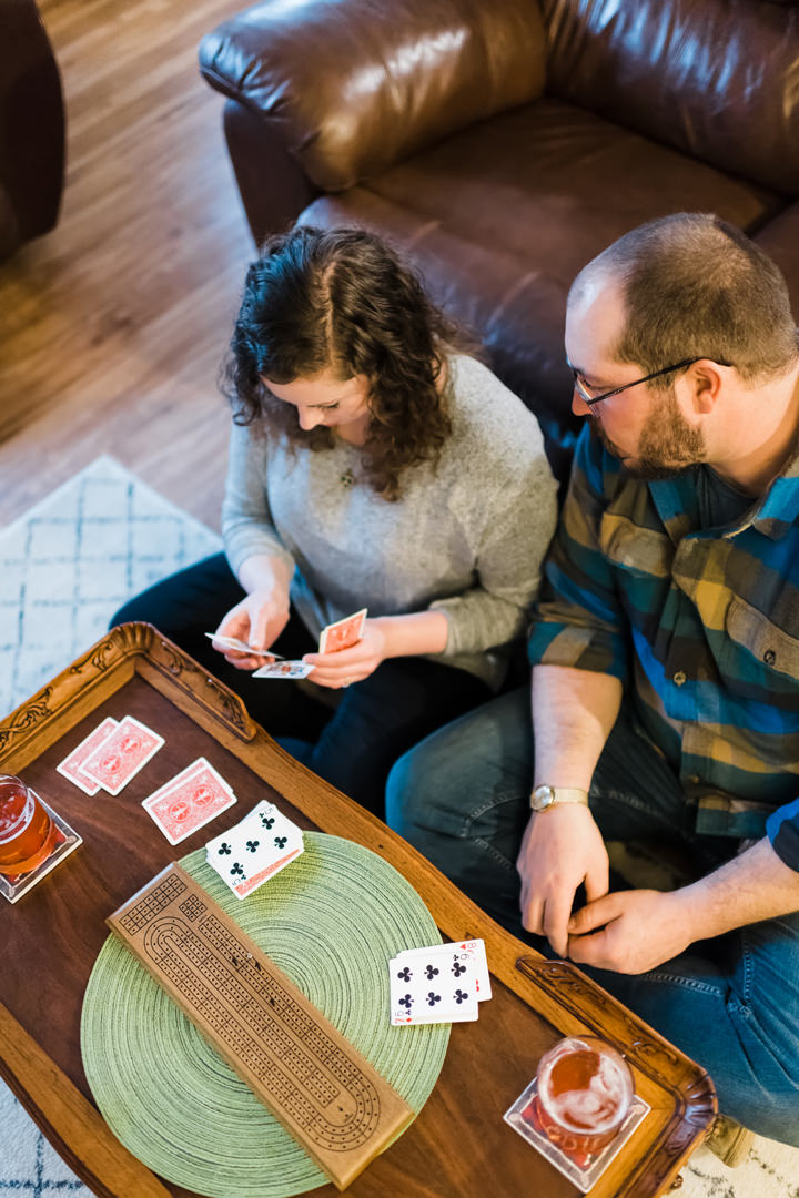 Man looks on as fiancé looks at her cribbage hand