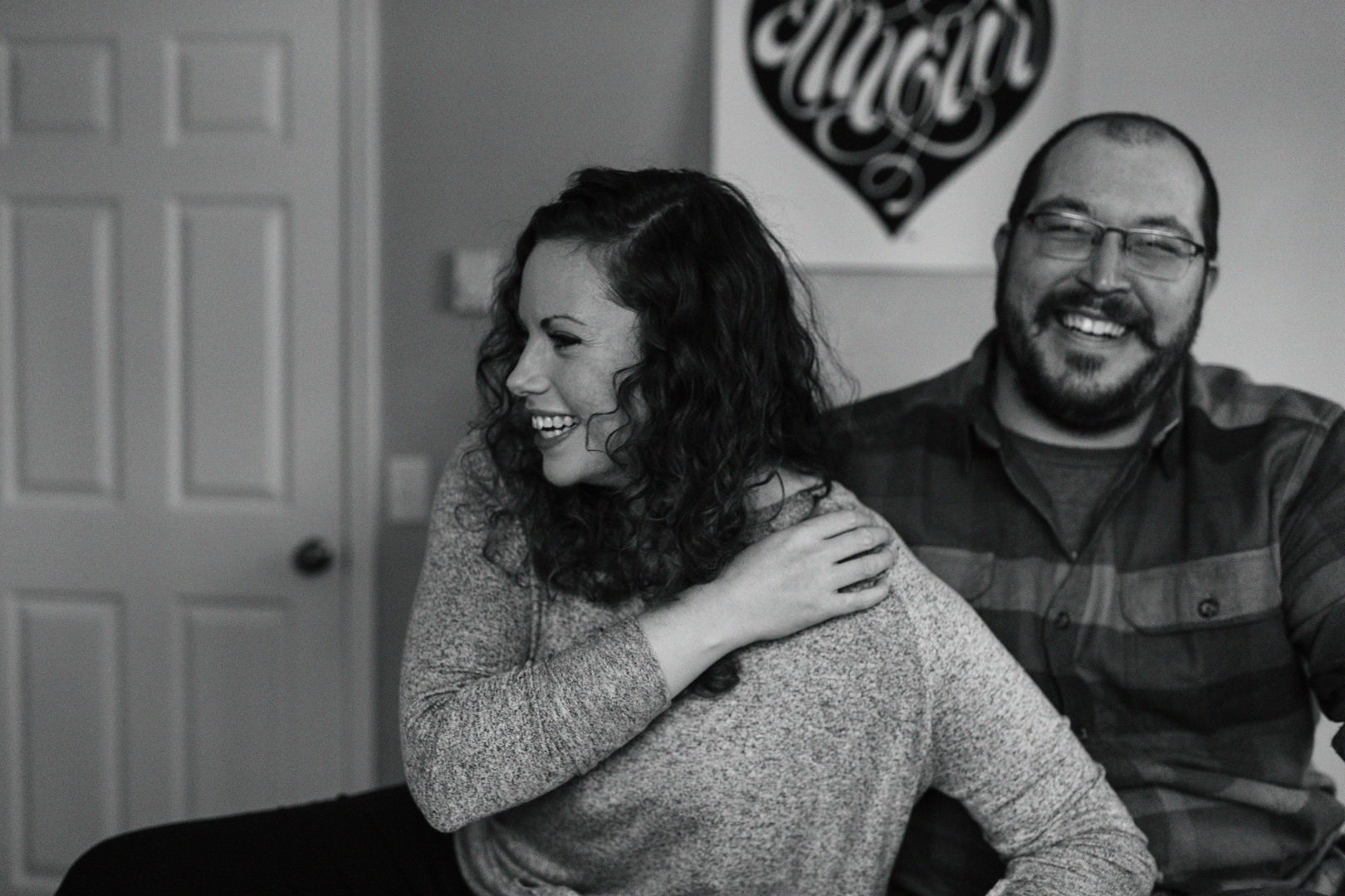 Engaged couple laughing on their bed