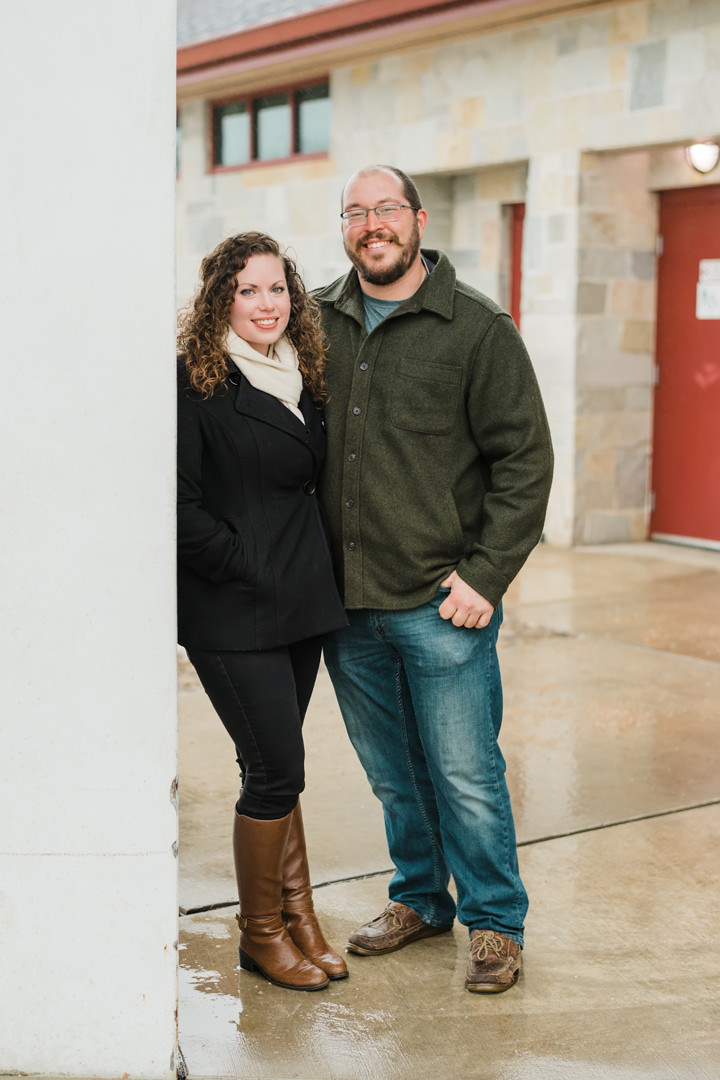 Engaged couple pose for a portrait against a pillar