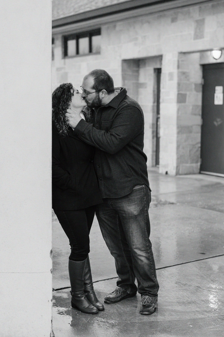Engaged couple leaning on a pillar and kissing