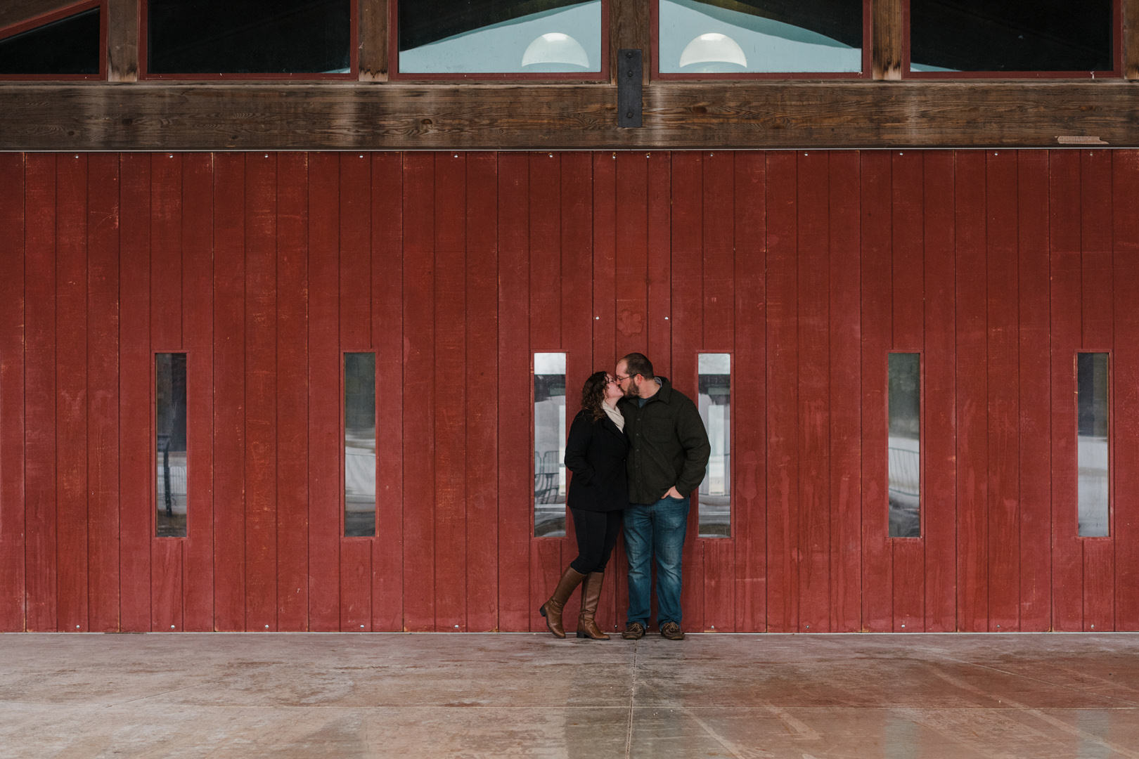 Engaged couple kissing in front of red barn wood building