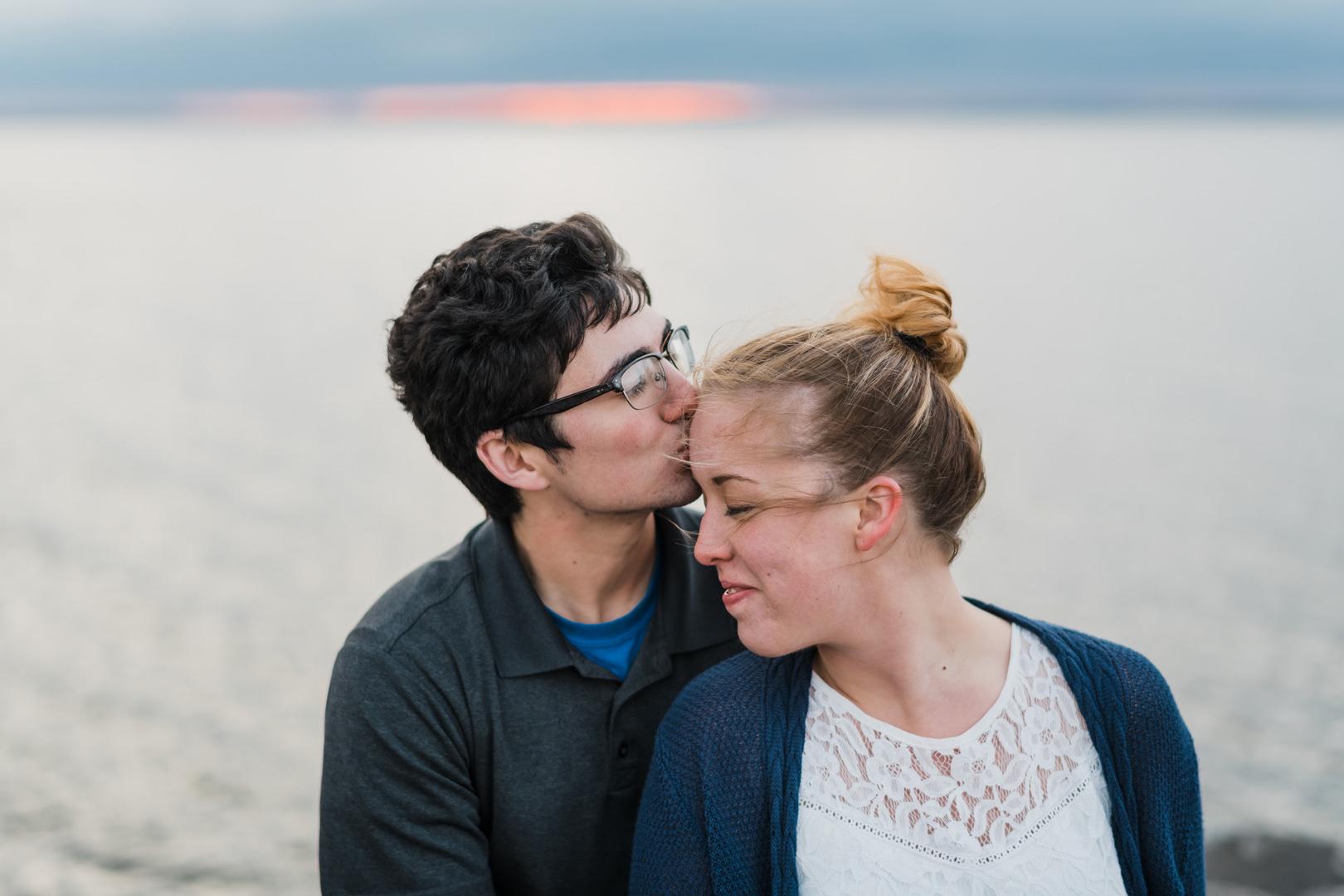 Man kisses fiance during sunset