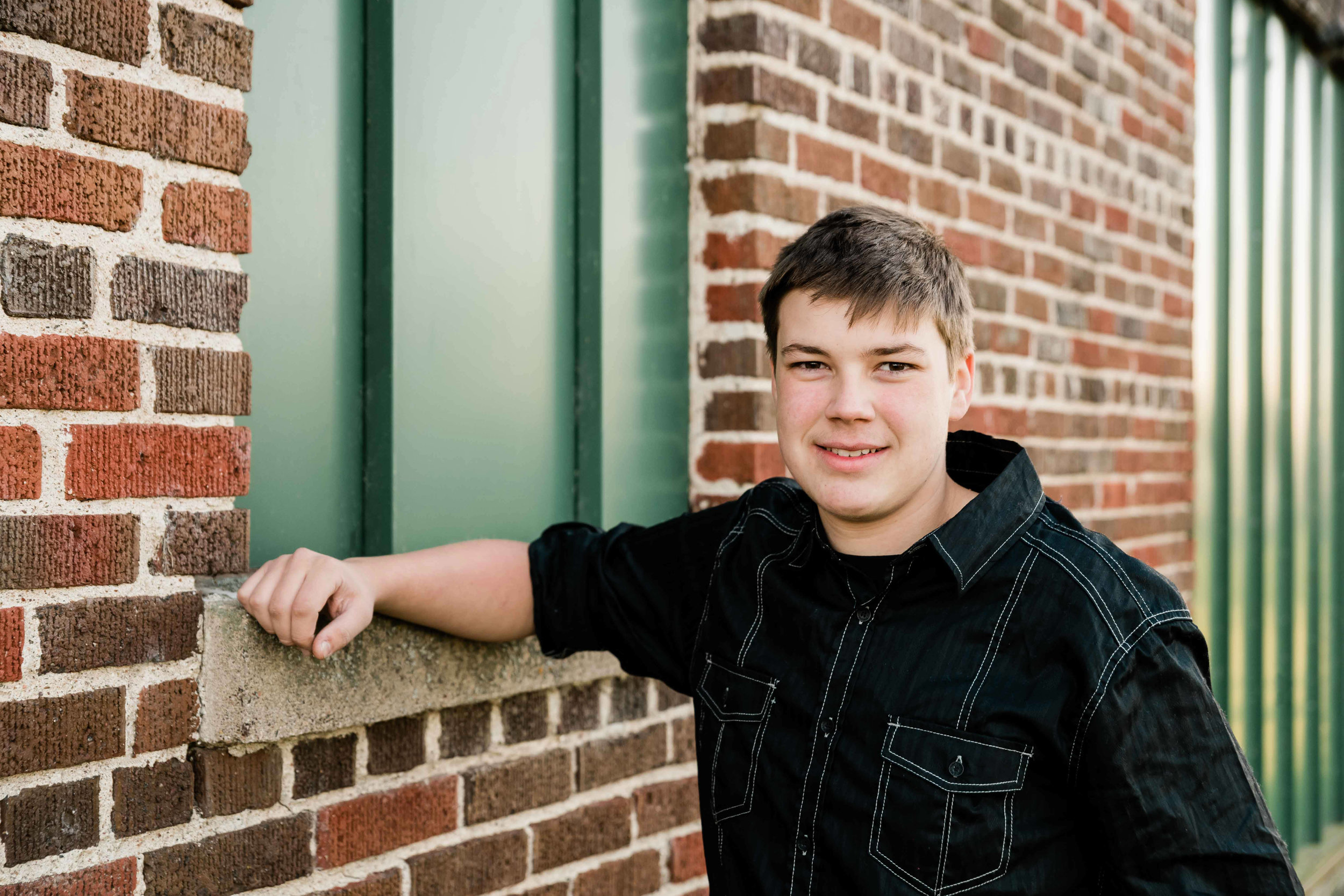 High school senior leans up against a brick building