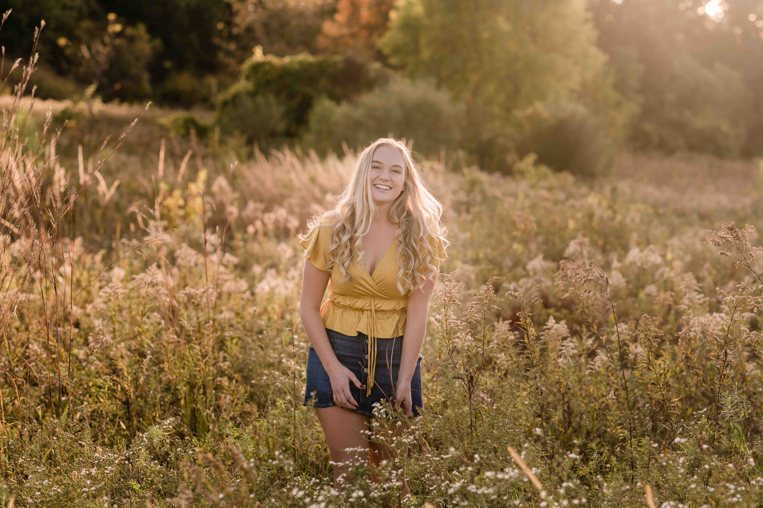 High school senior laughs in a field