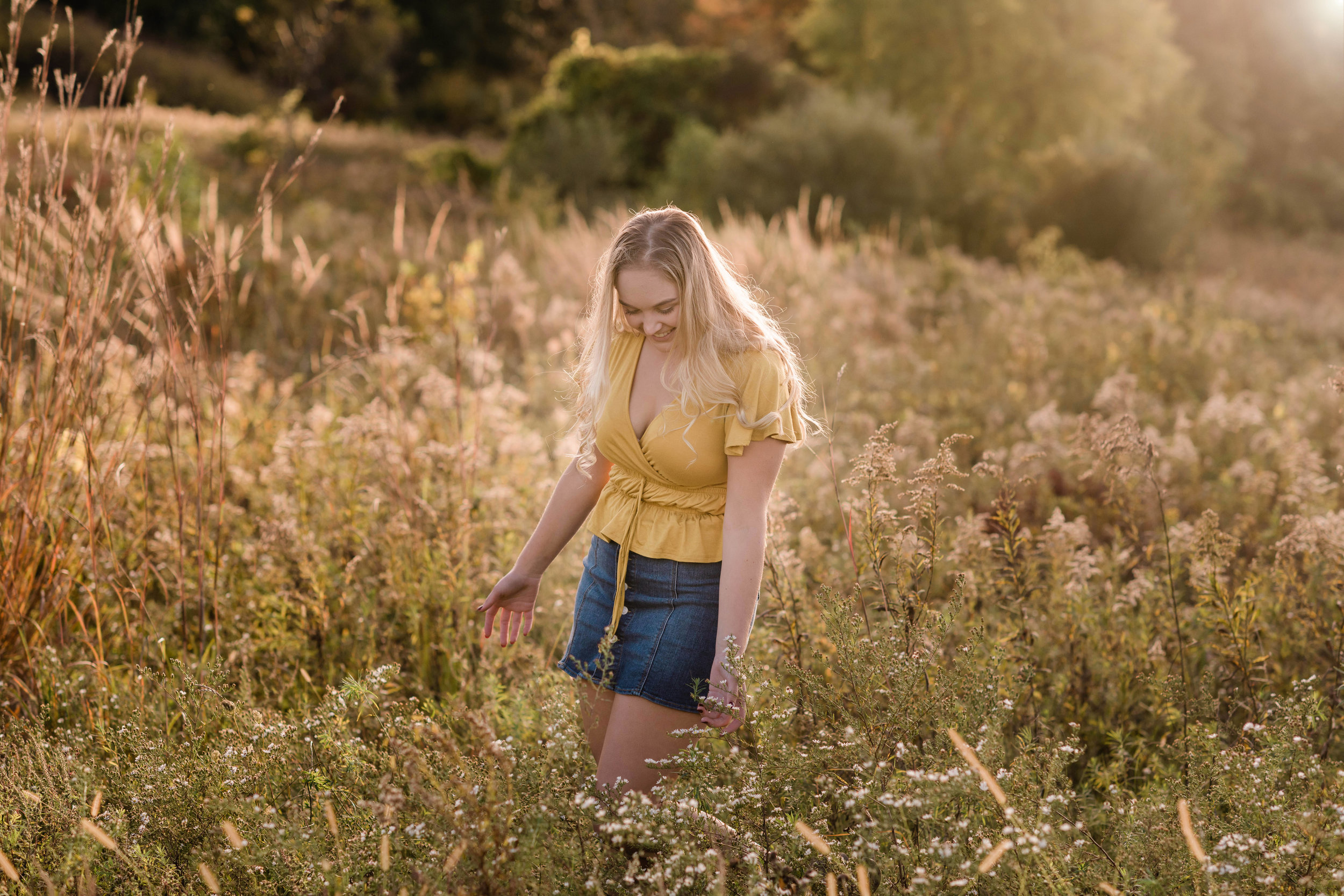 High school senior touching long grass