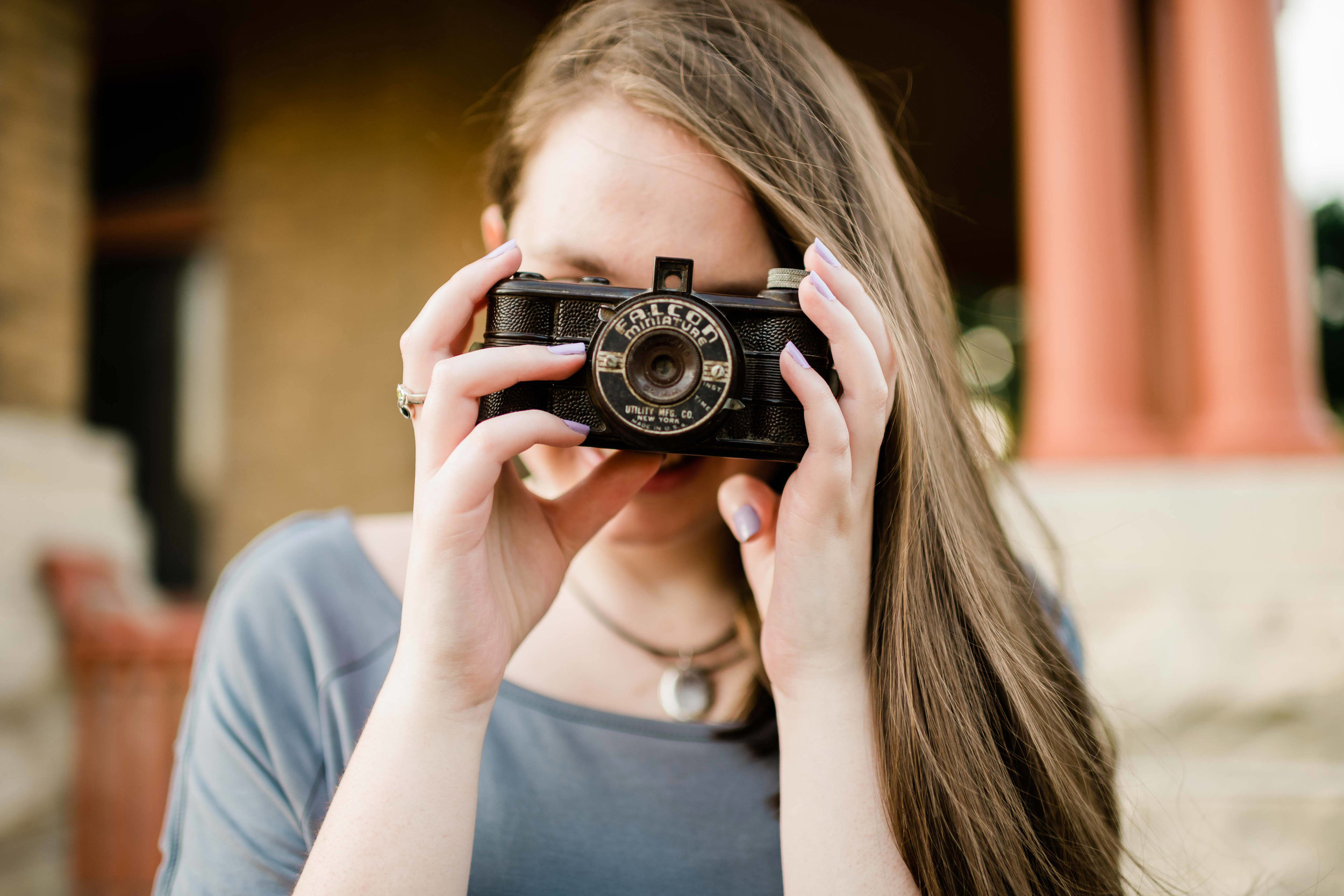 High school senior holding a camera up to her face