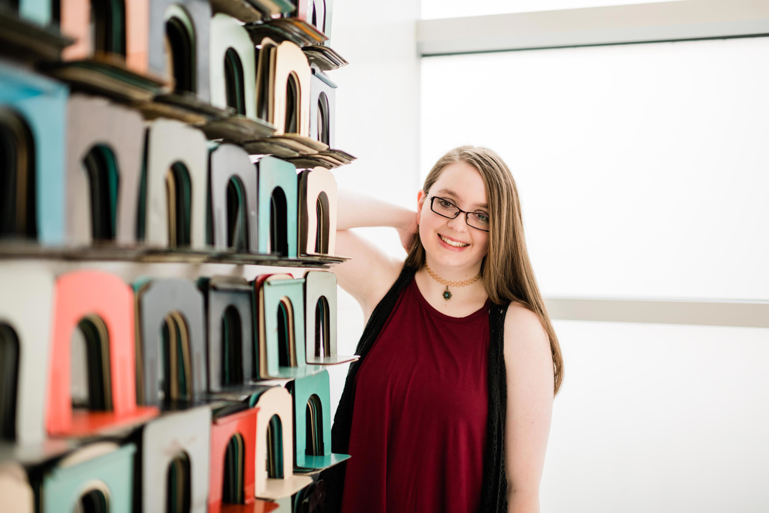 High school senior leaning up against a wall display of colorful bookends