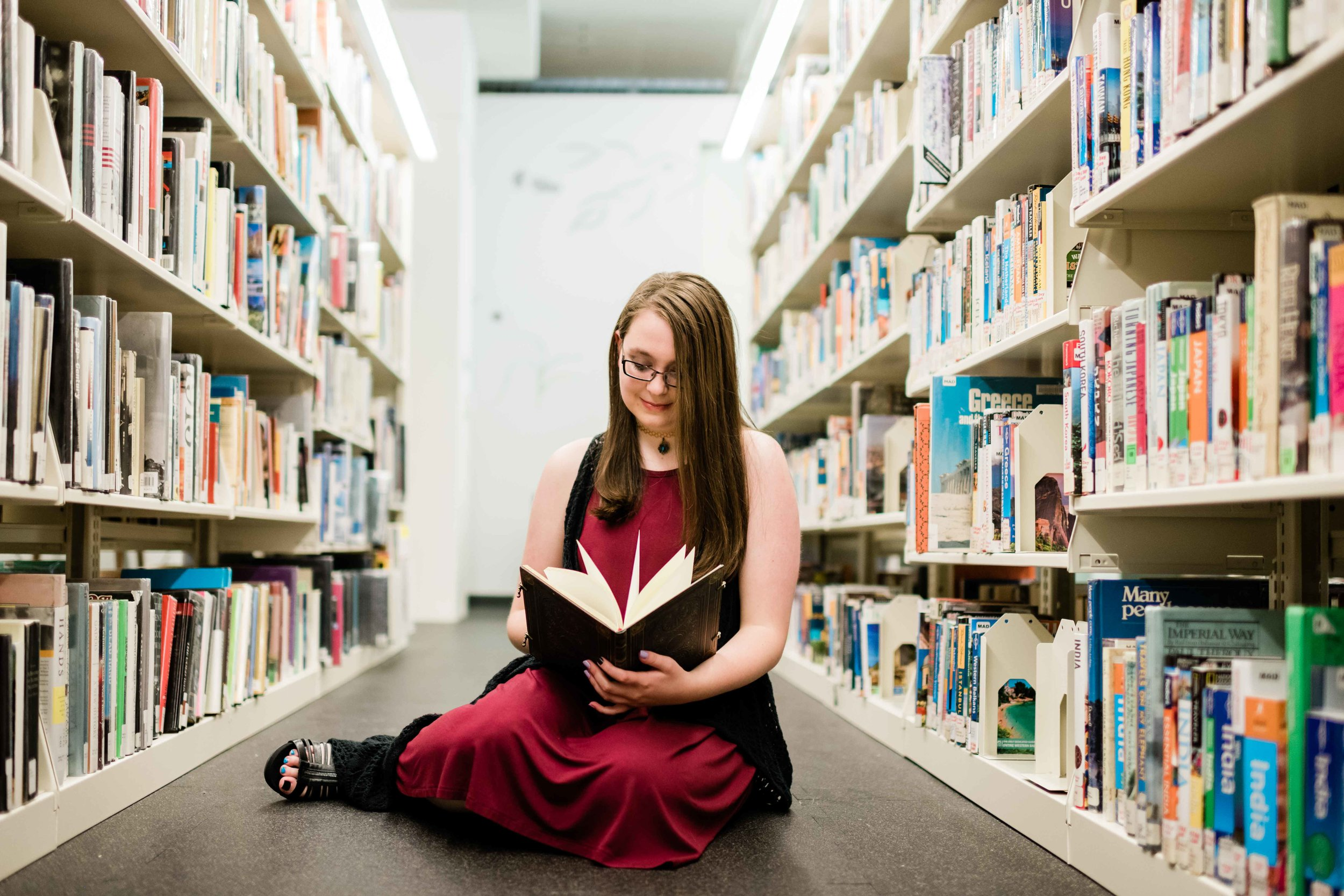 High school senior reading a book in the stacks at Madison Public Library
