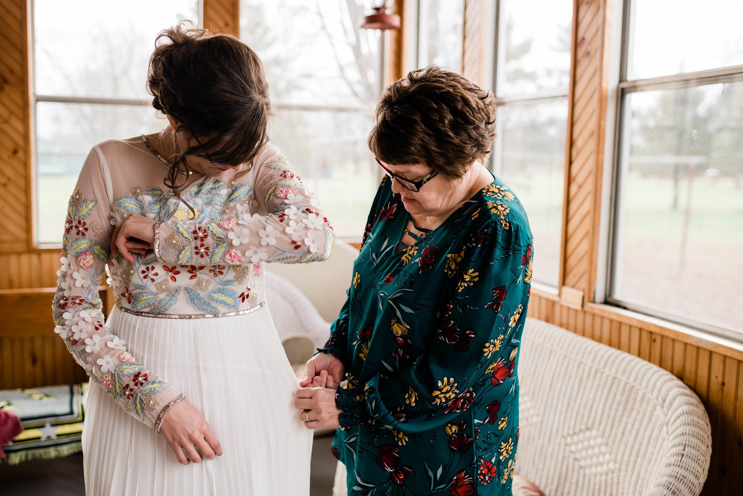 Mother helps her daughter zip up her wedding dress
