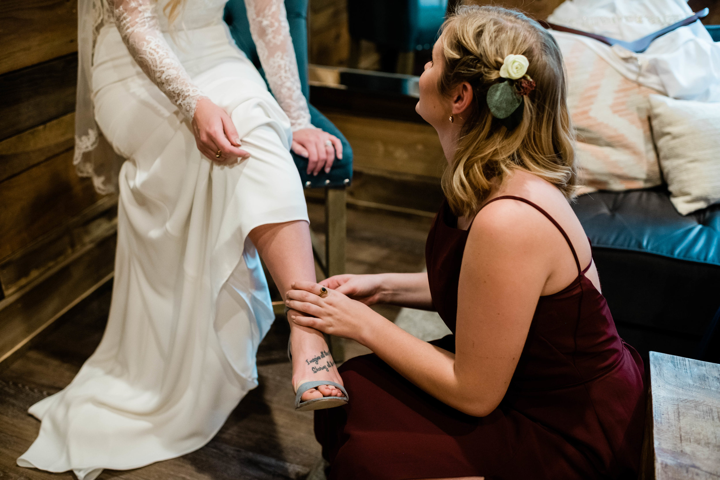 Bridesmaid helping put bride's shoe on