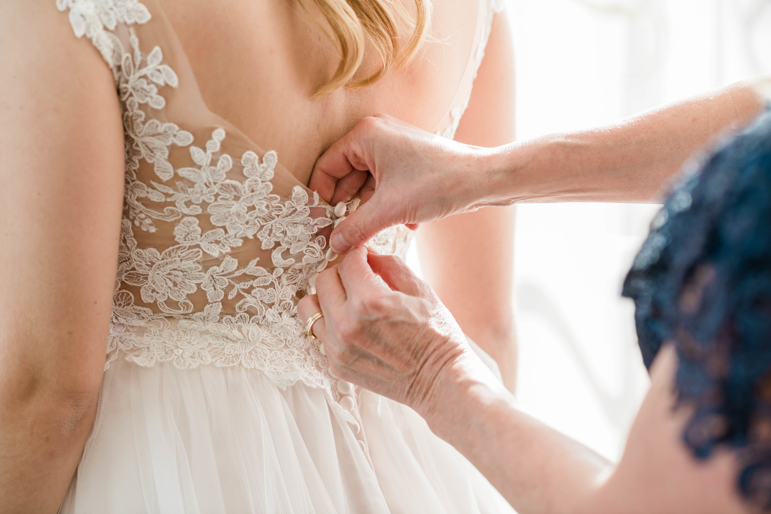 Mother buttoning up the bride's wedding dress