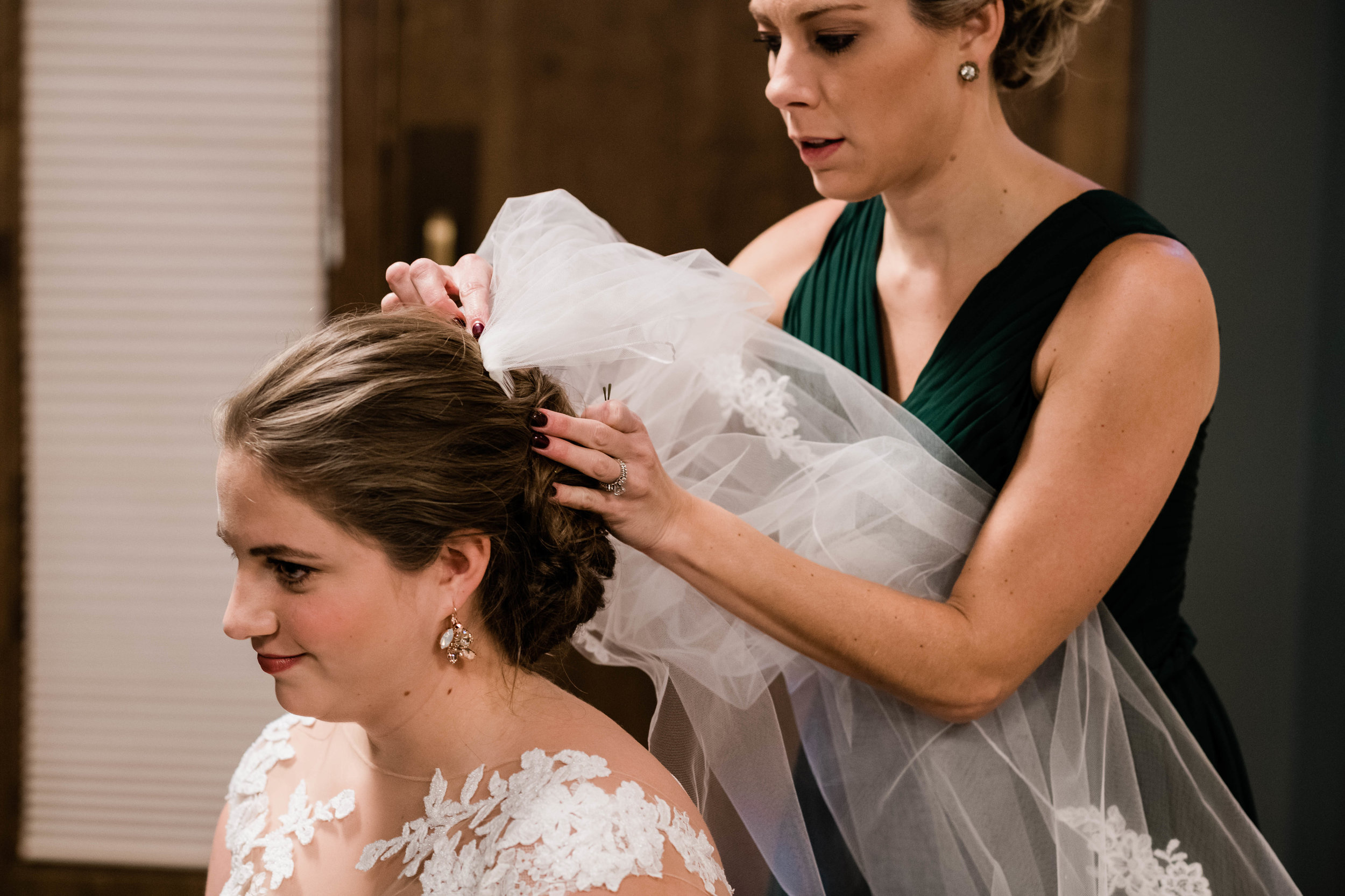Bridesmaid putting bride's veil on