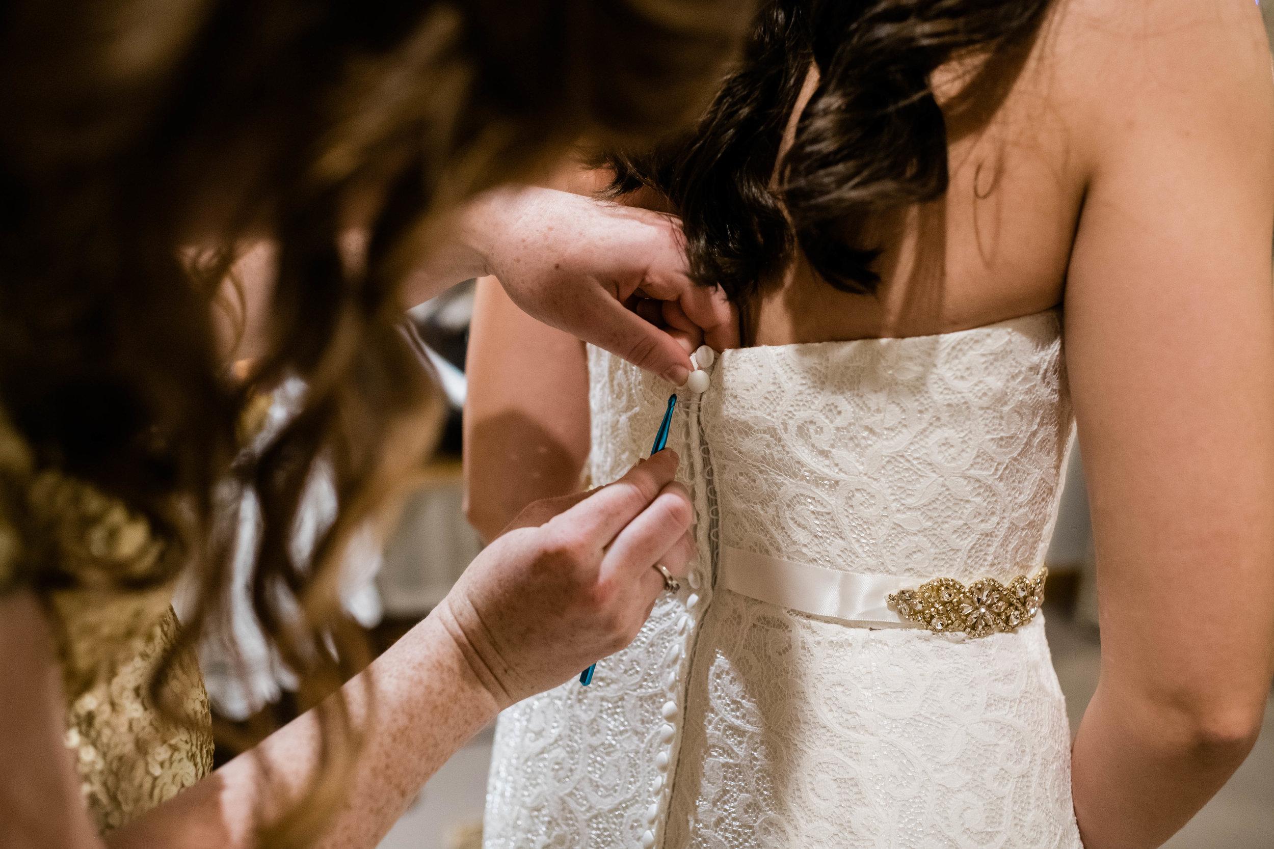 Bridesmaid using crochet hook to fasten bride's wedding dress