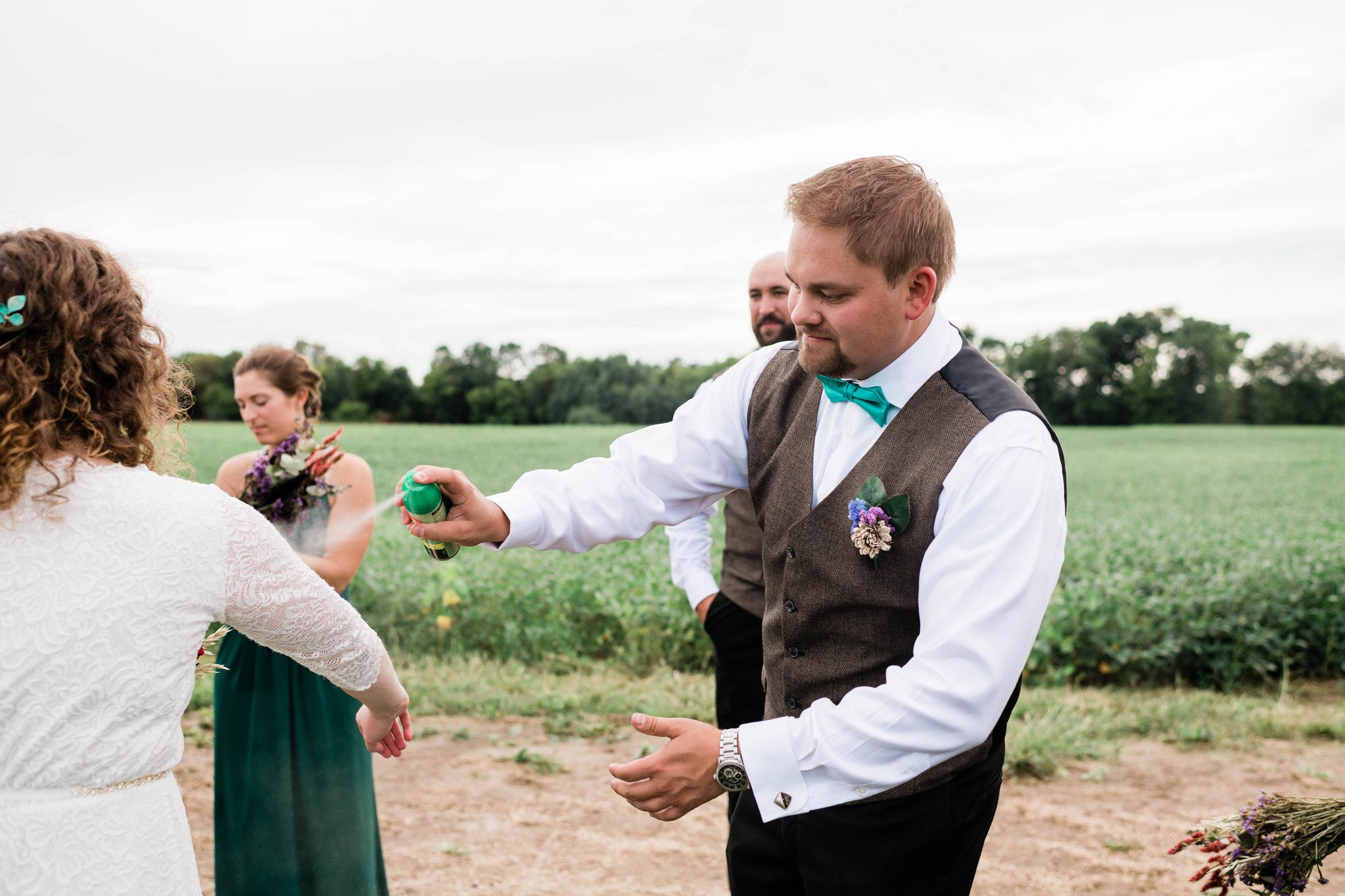 Groomsmen spraying bride with bug repellant