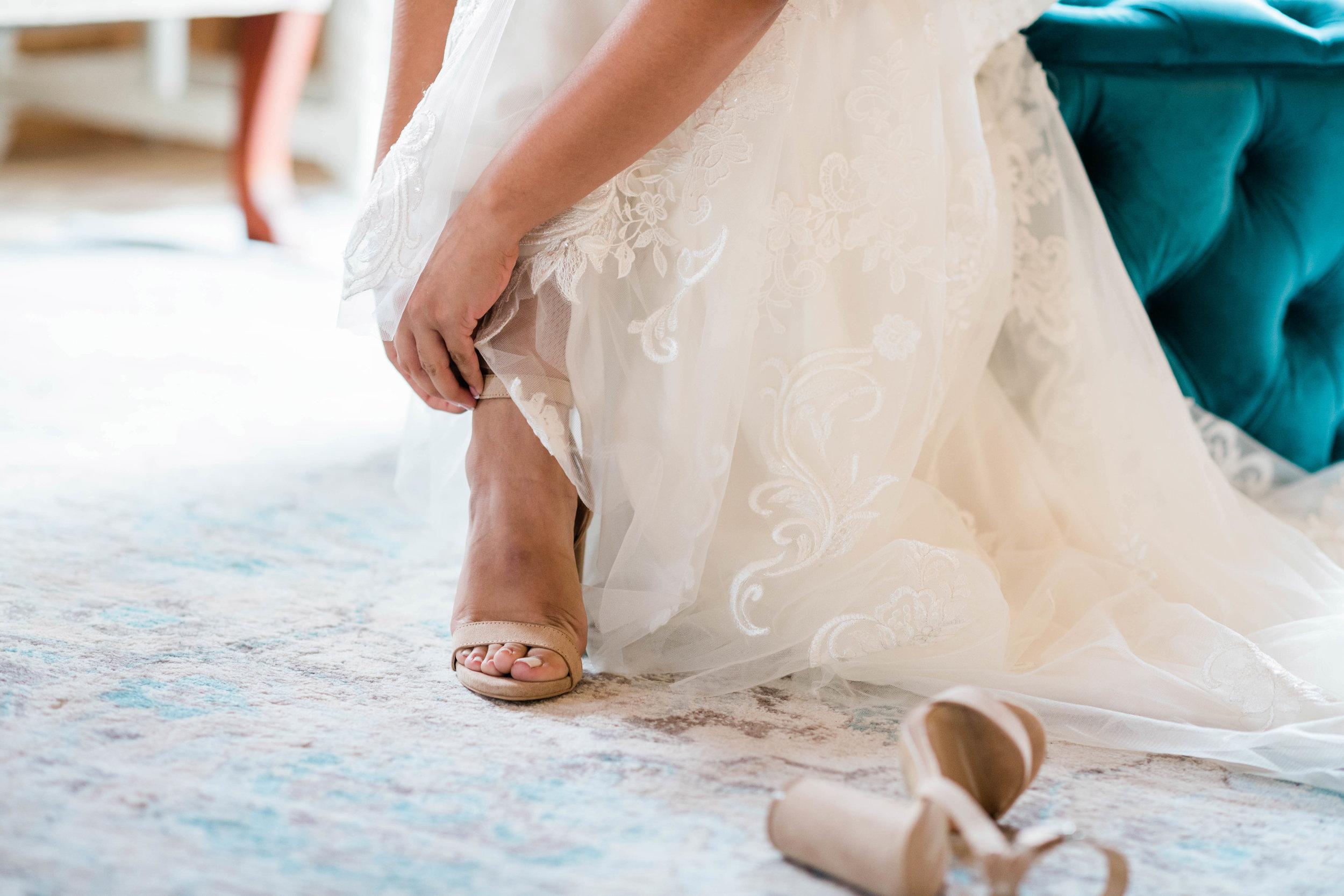 Bride fastening her shoe strap