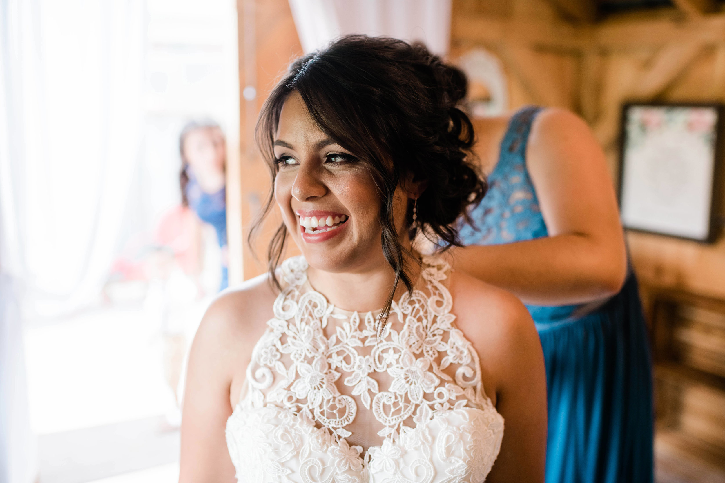 Bride smiles as her dress gets fastened