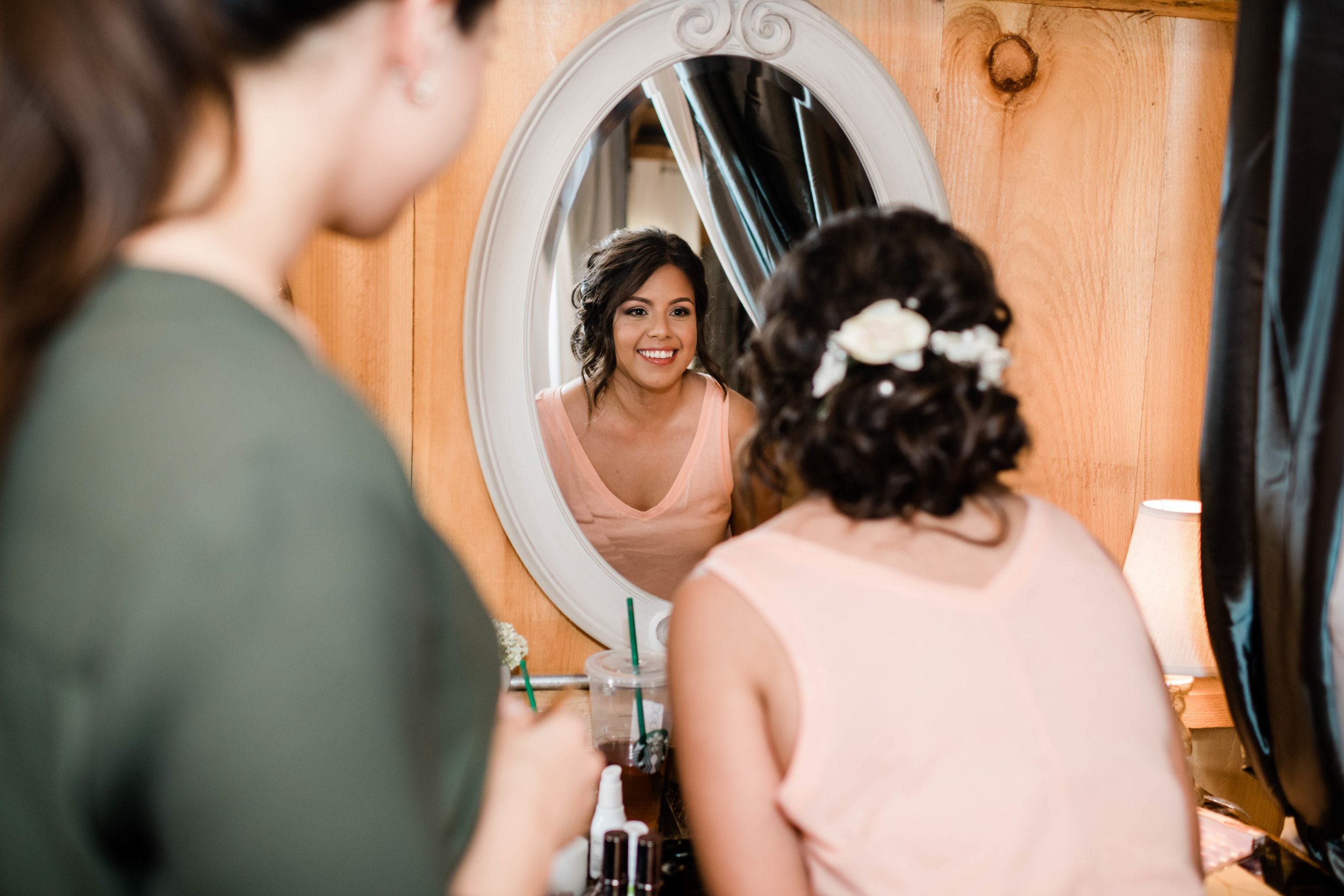 Bride looks happily in the mirror at her wedding day hair and makeup