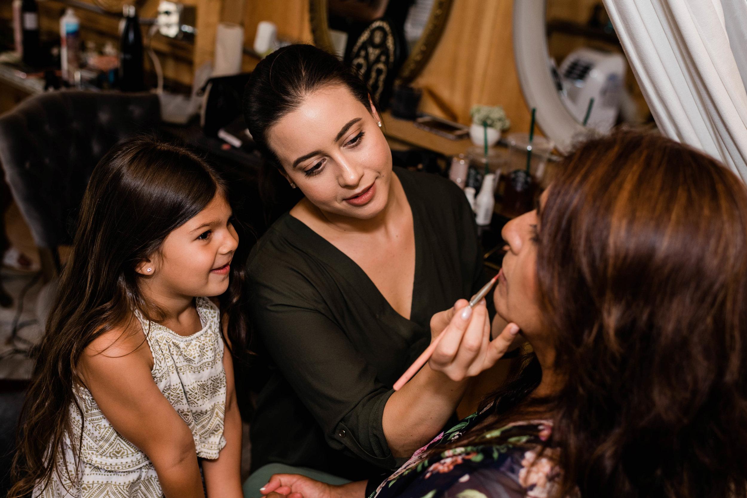 Flower girl watches makeup artist apply makeup