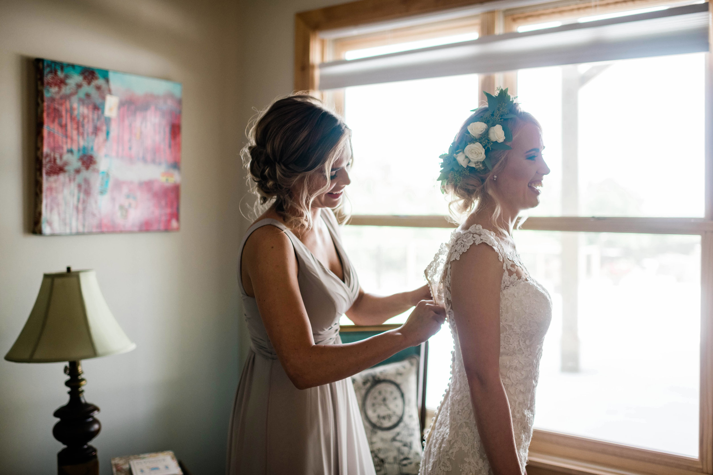 Bridesmaid helps bride with her dress