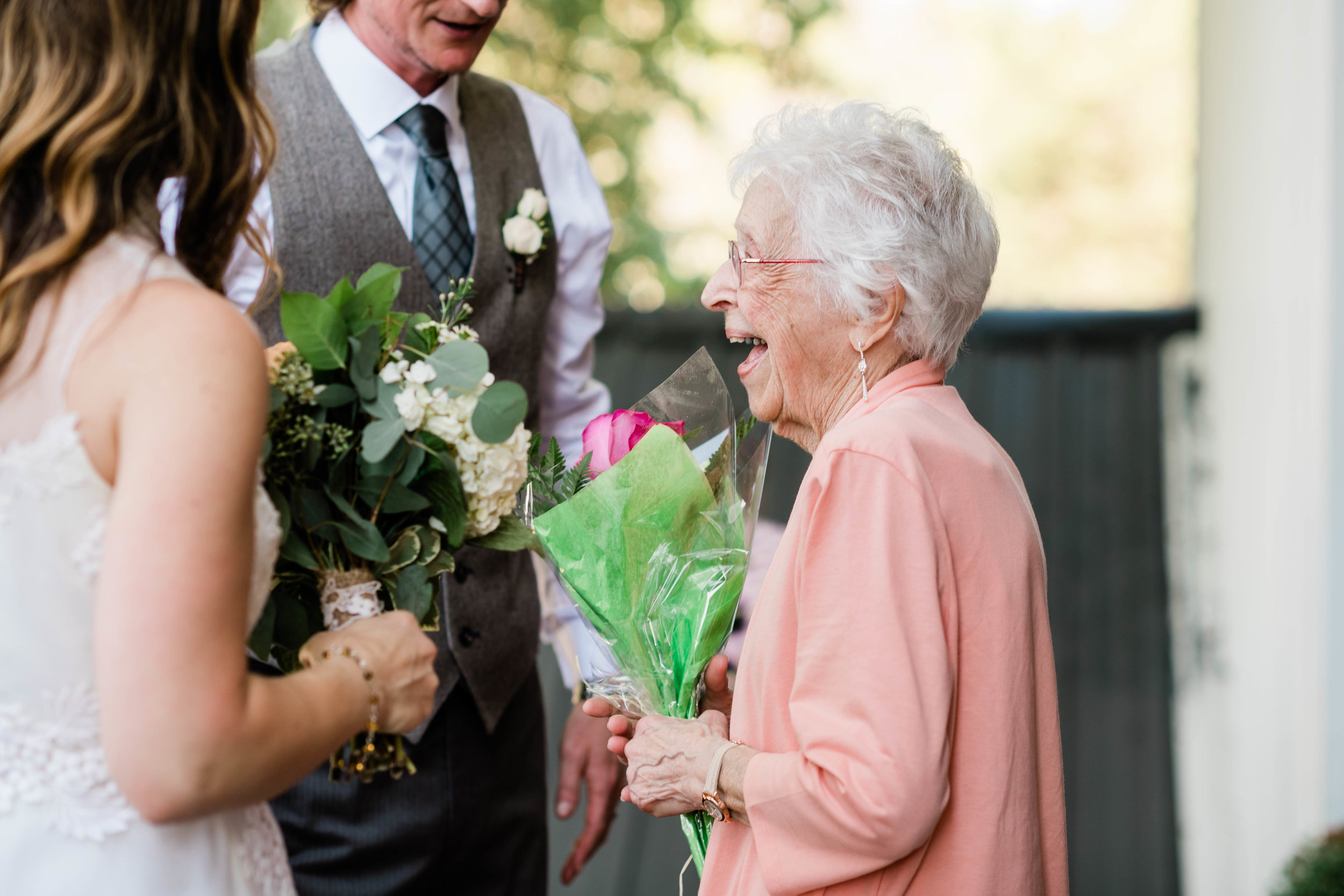 Grandma laughing with bride and groom