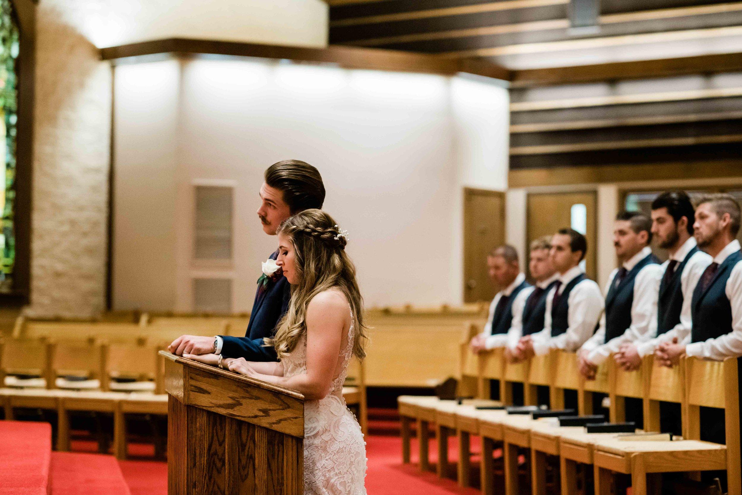 Bride and groom kneel during Catholic wedding ceremony