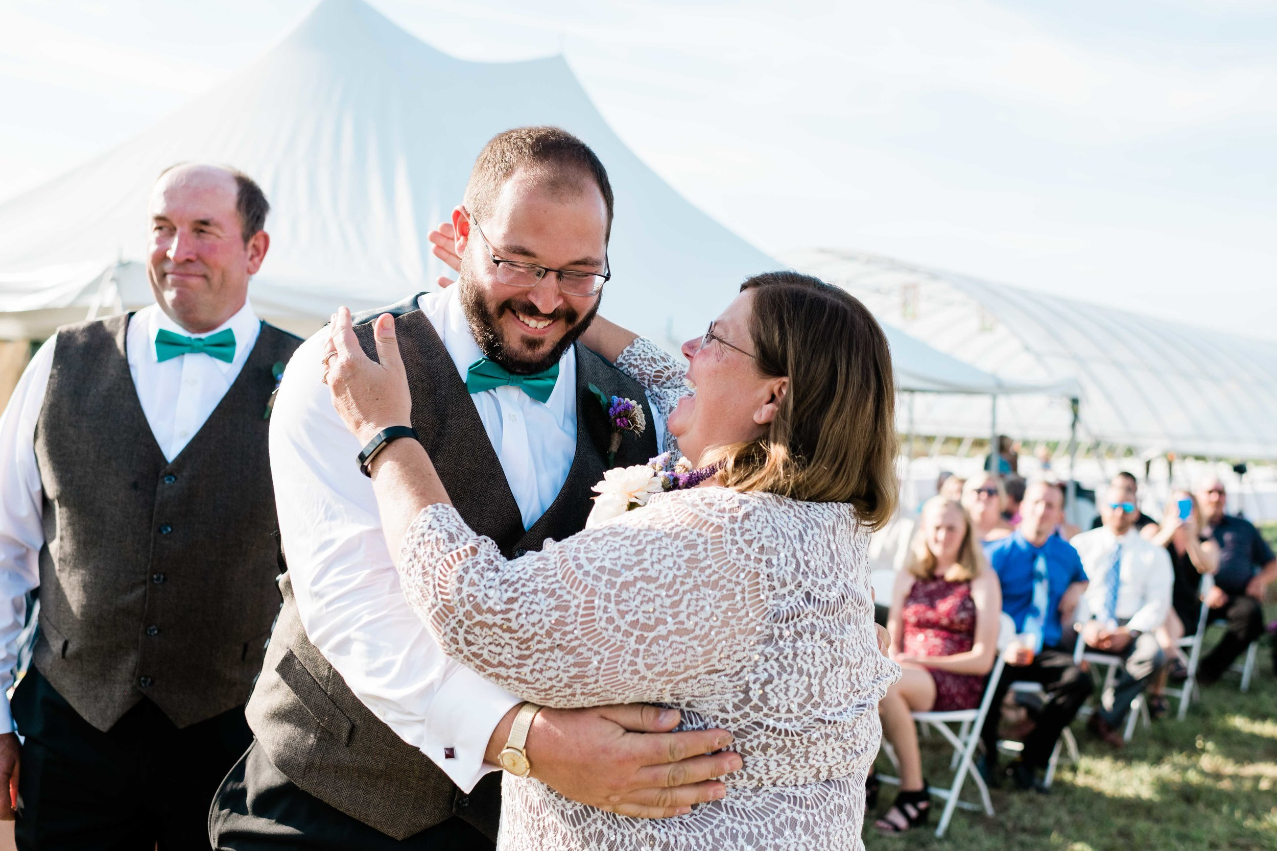 Groom and his mom share a laugh and a hug after they walk down the aisle together