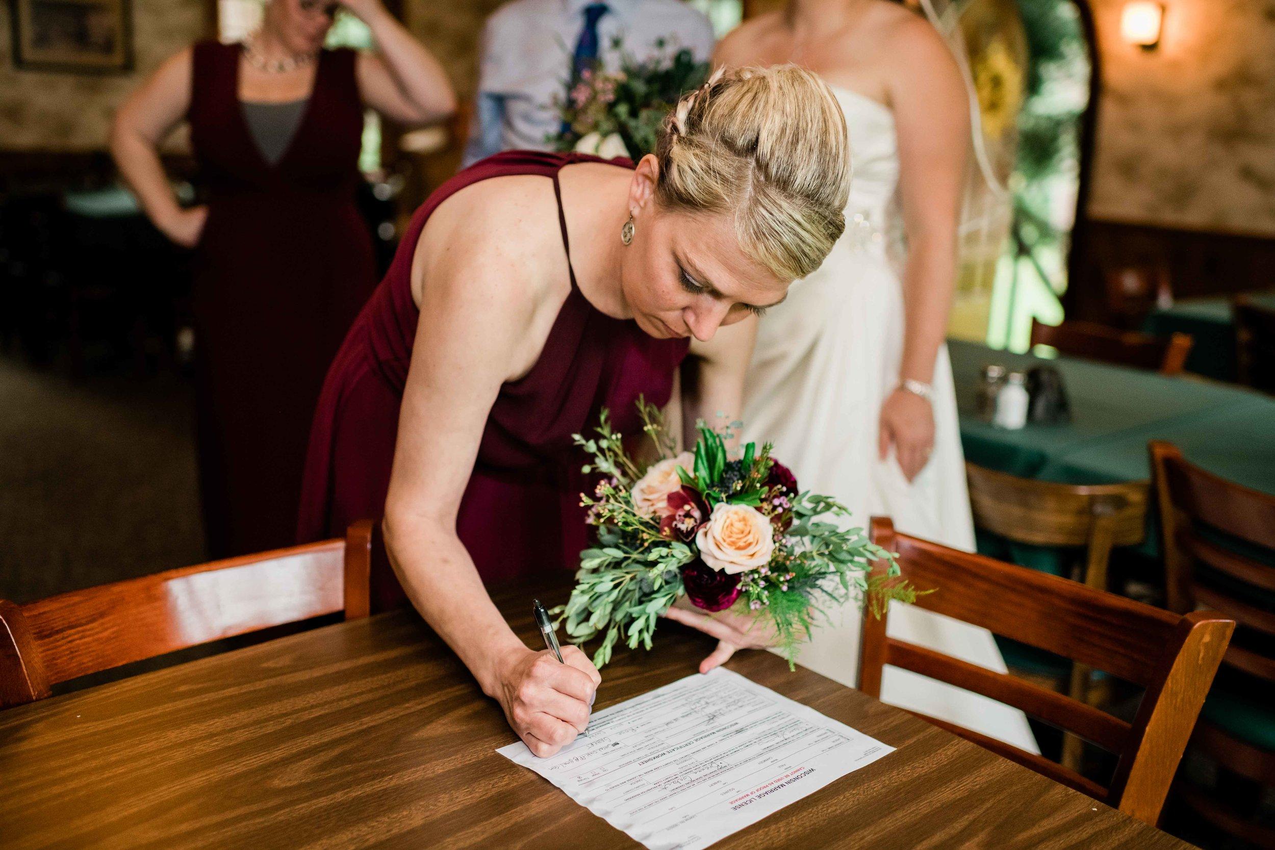 Bridesmaid signs marriage license
