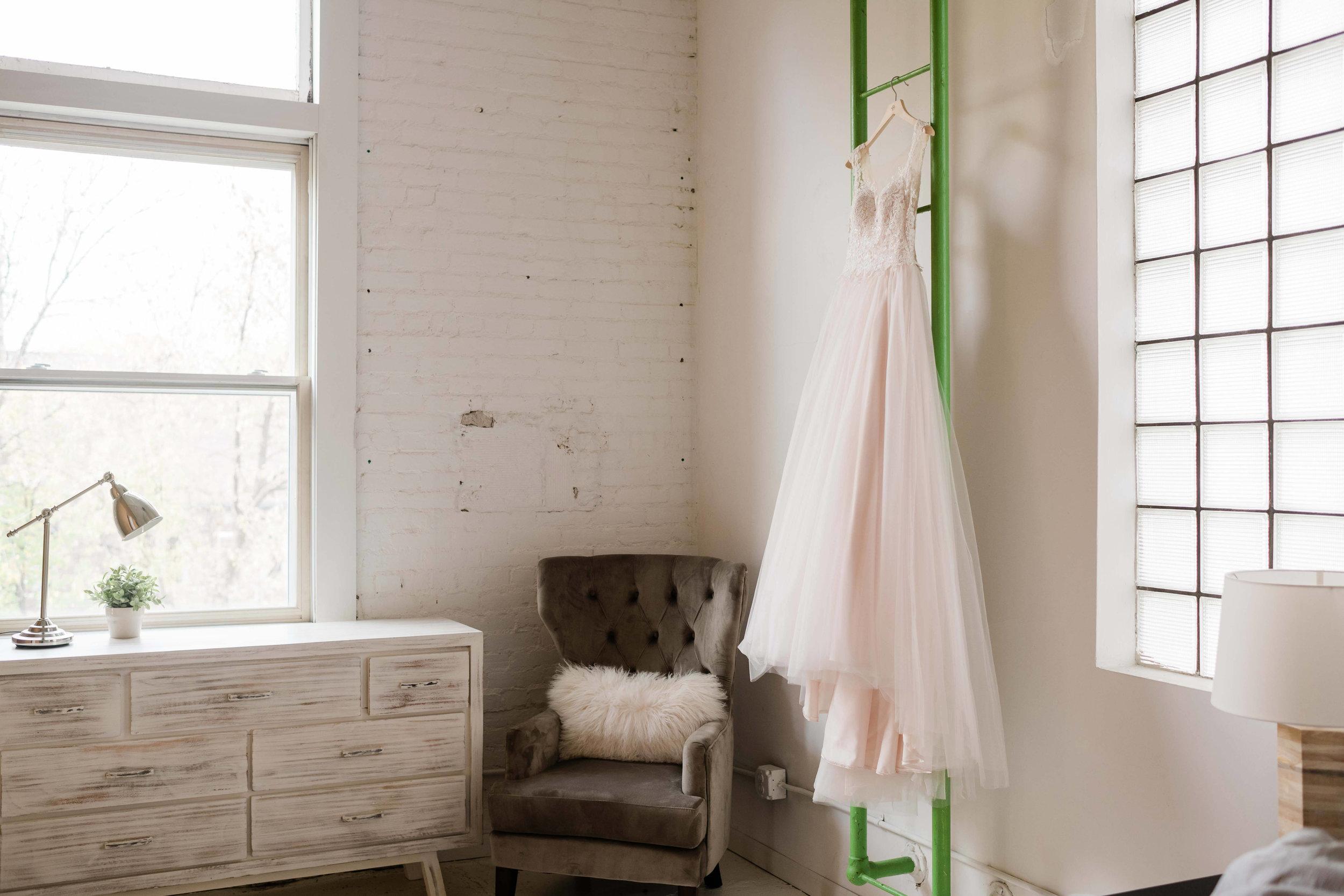 Blush pink wedding dress hanging on green ladder