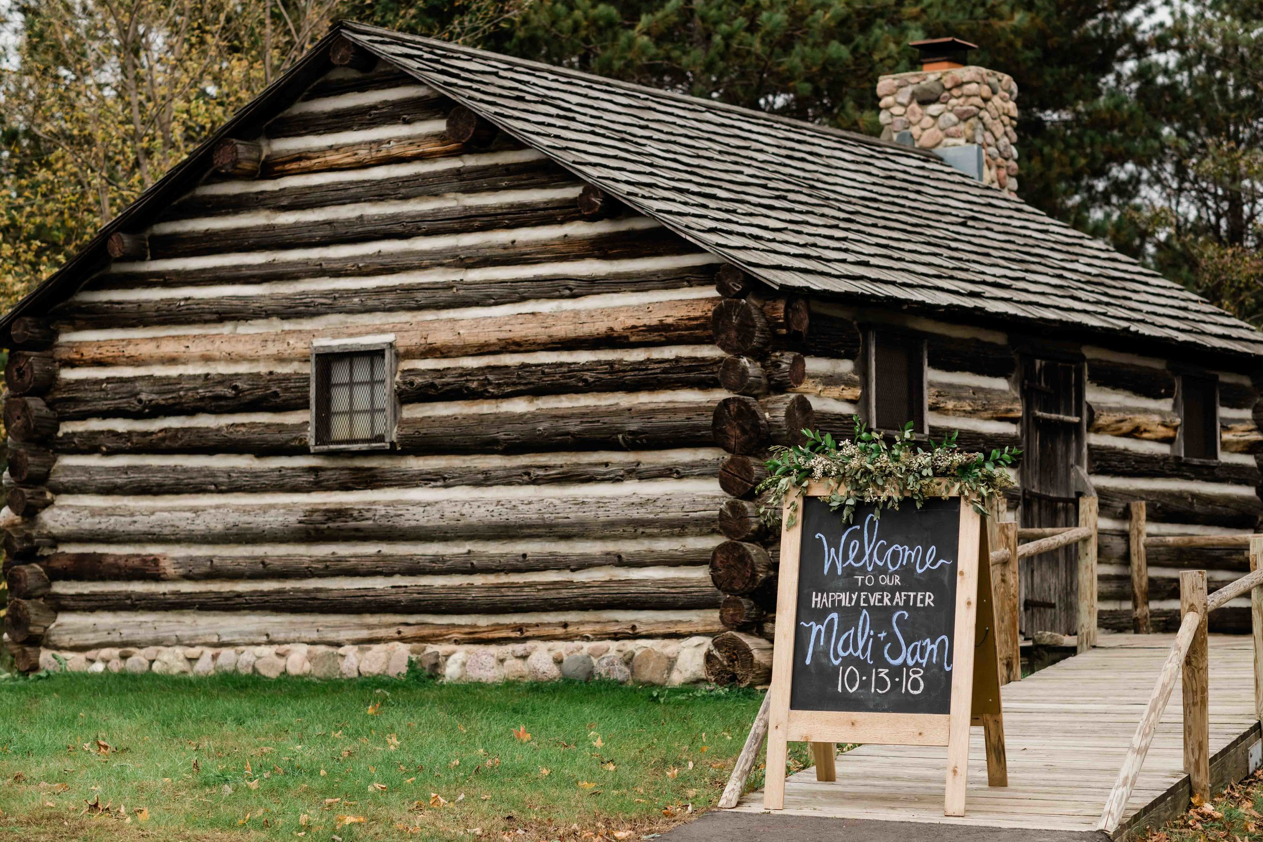 Wedding sign in front of log cabin
