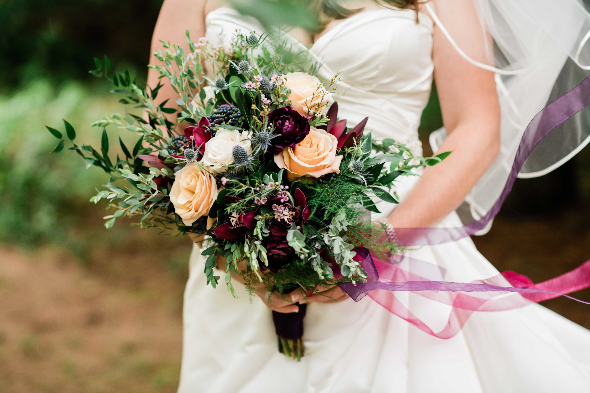 Bride's veil blows in the wind as she holds her bouquet