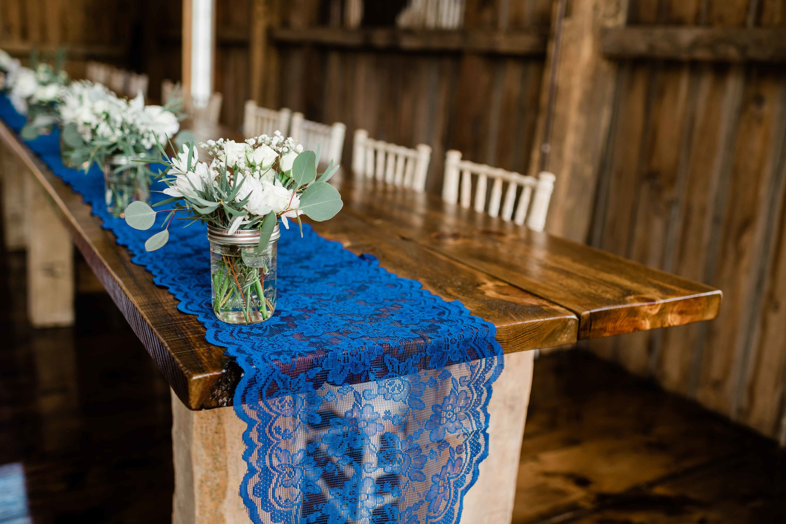 Blue lace table runner under jars of flowers