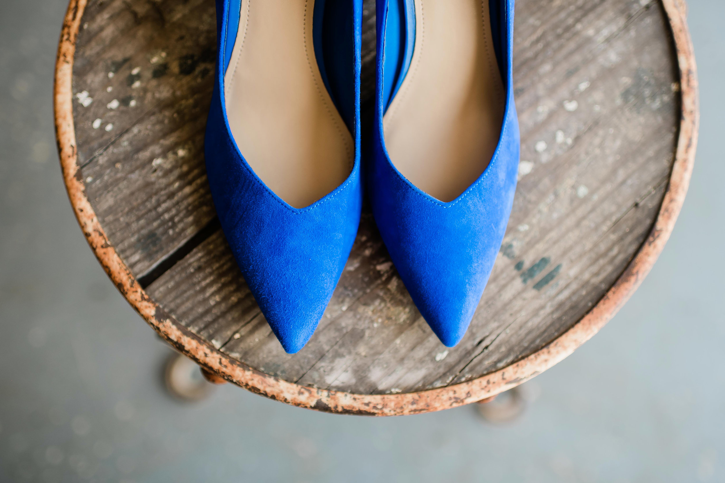 Blue bridal shoes sitting on rusty chair