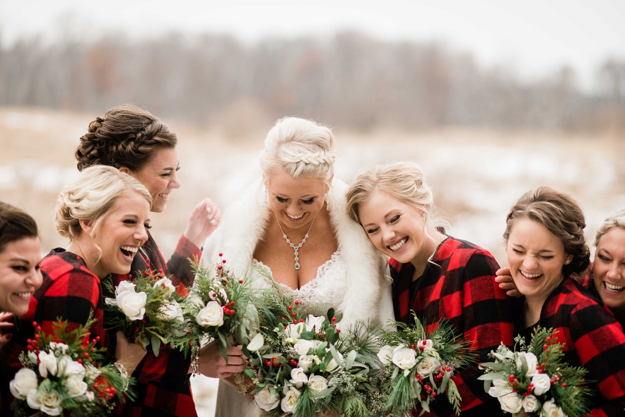 Bride and bridesmaids laughing as they huddle for warmth