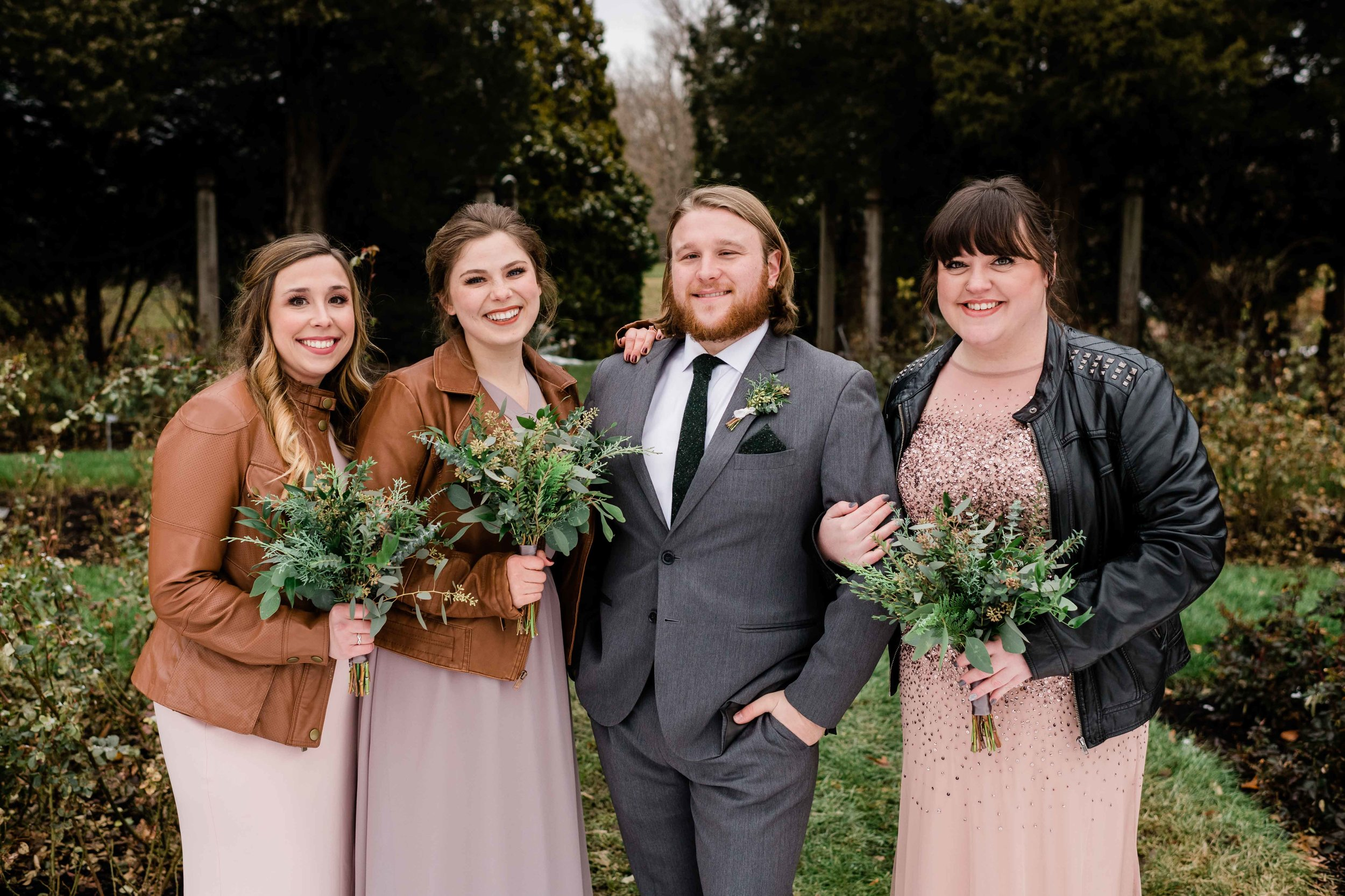 Groom poses with bridesmaids