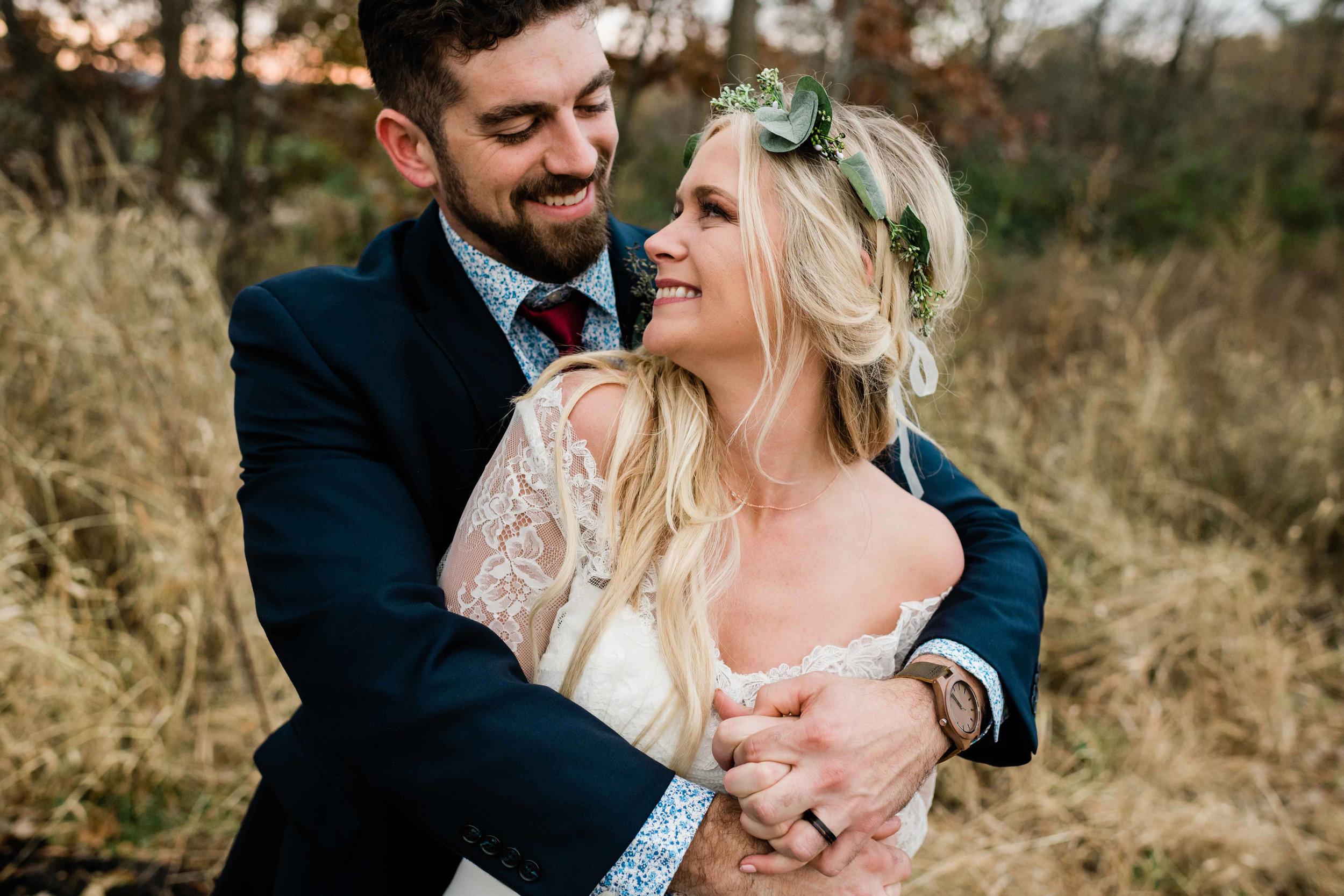Groom wraps his arm around bride from behind