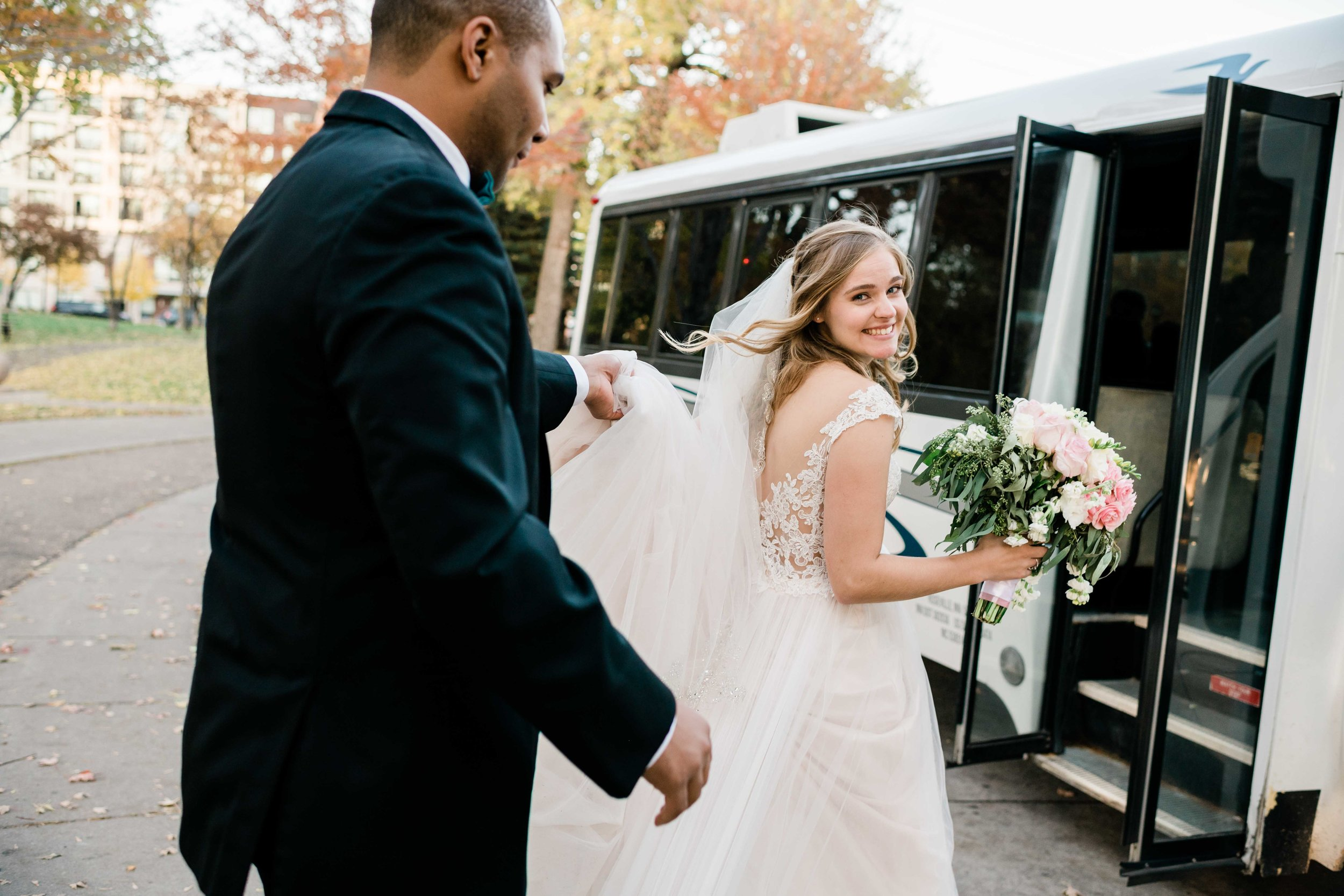 Groom holding up bride's veil as they approach shuttle bus