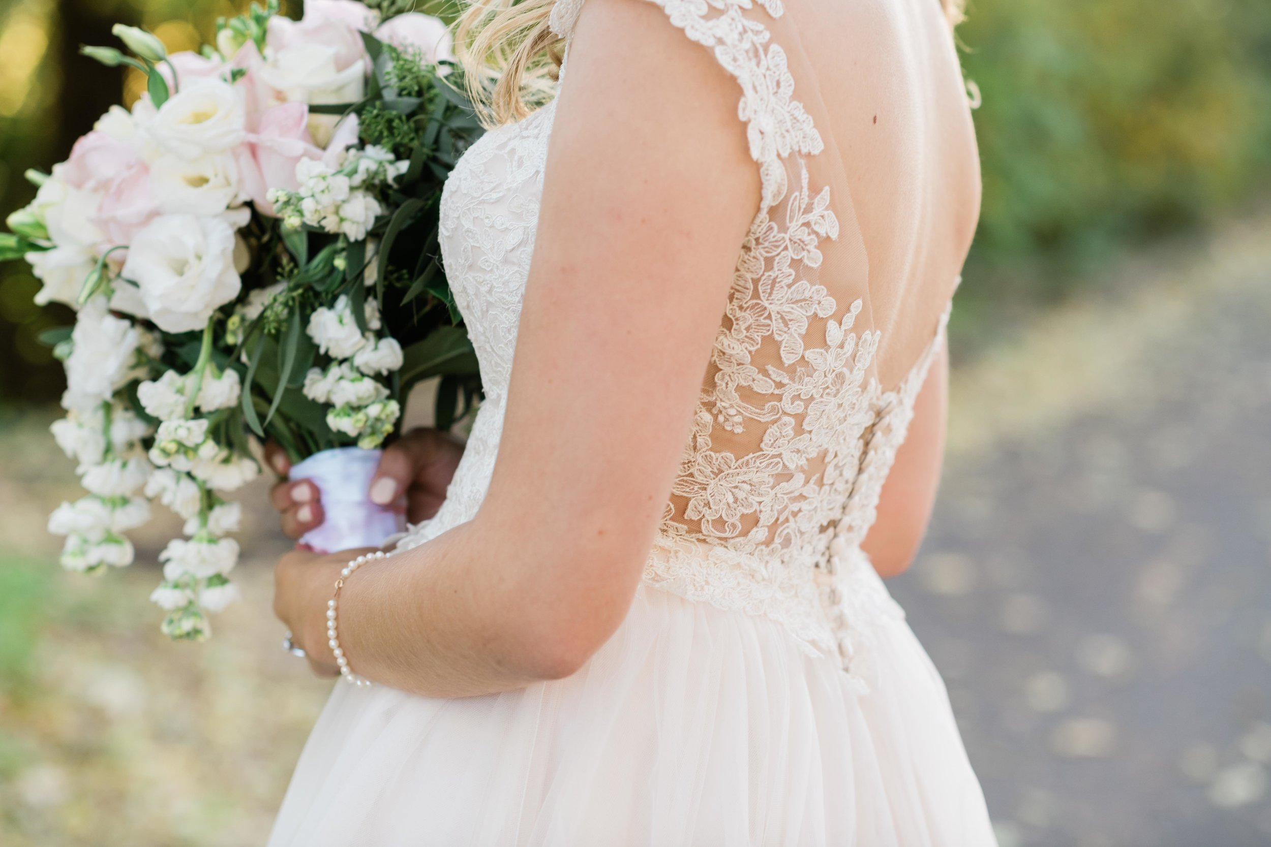 Back of bride's dress as she holds her bouquet