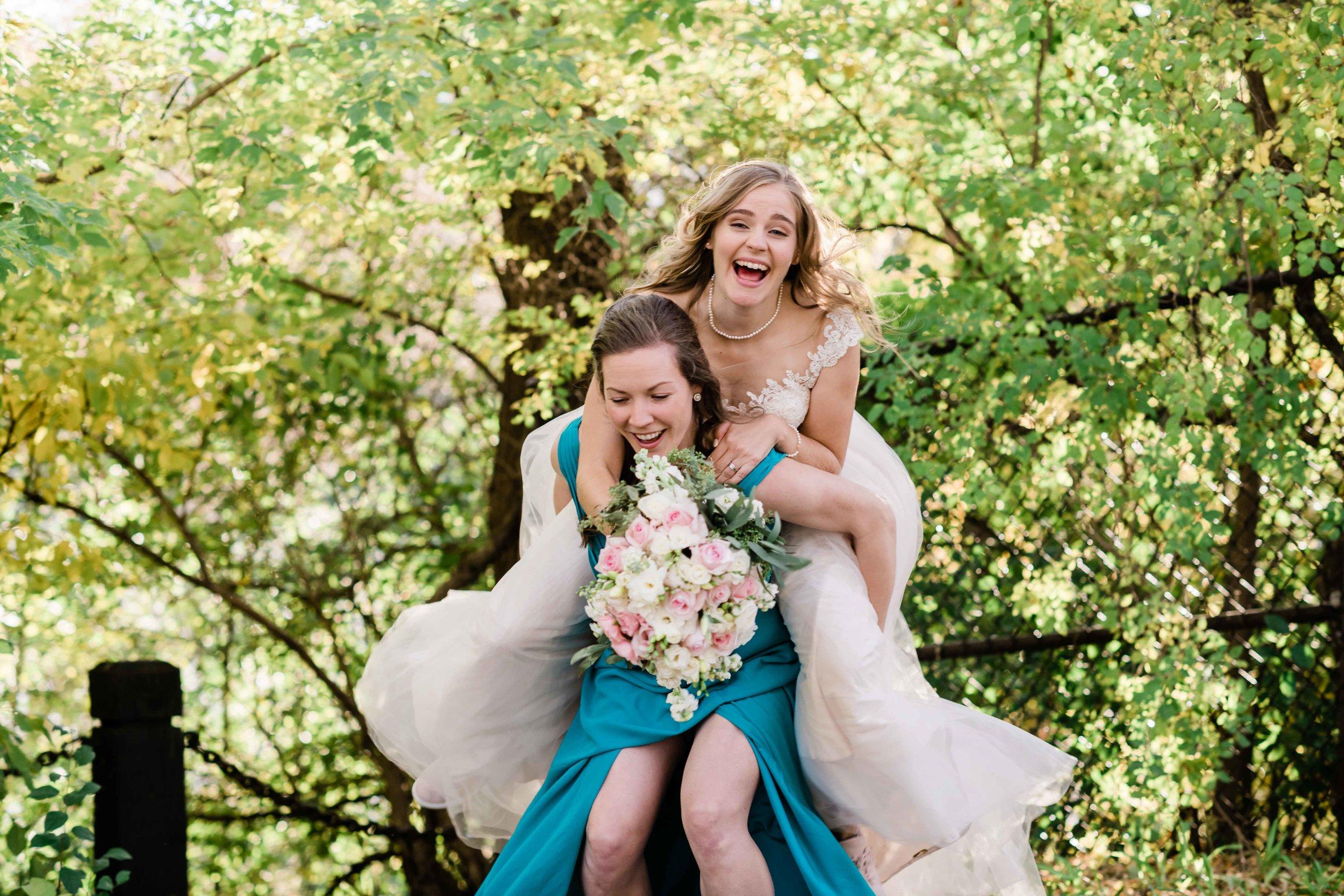 Bridesmaid gives bride piggy back ride