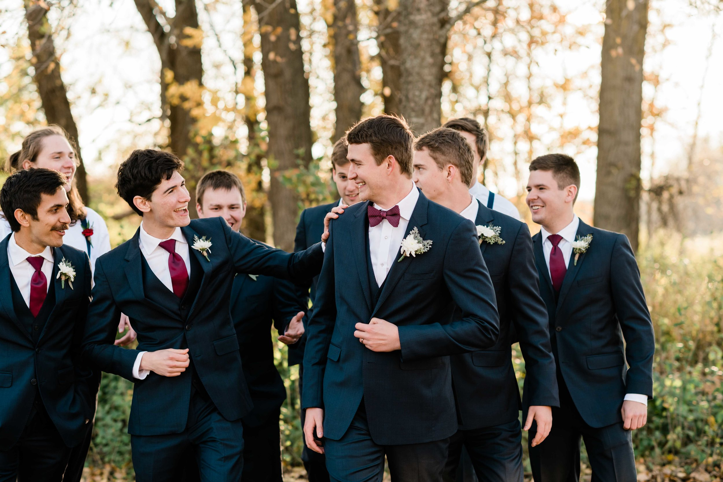 Groom and his groomsmen walking and laughing