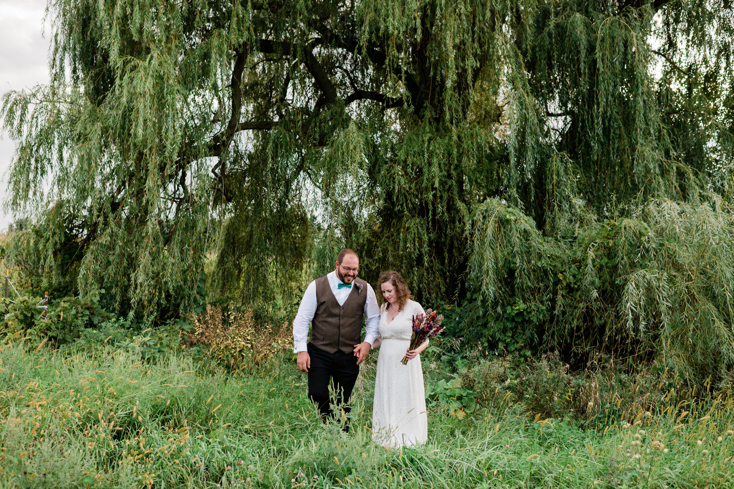 Bride and groom walk in front of a weeping willow tree