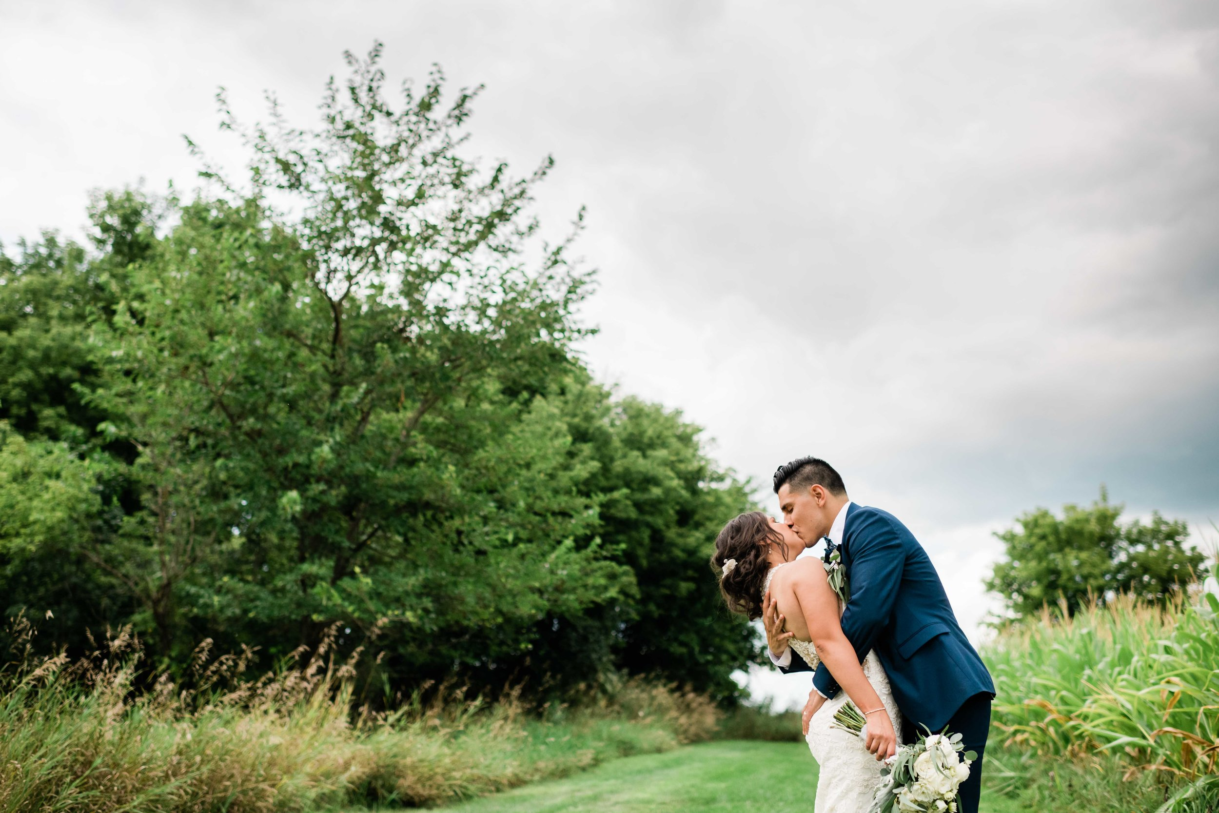 Groom kisses bride as he dips her back