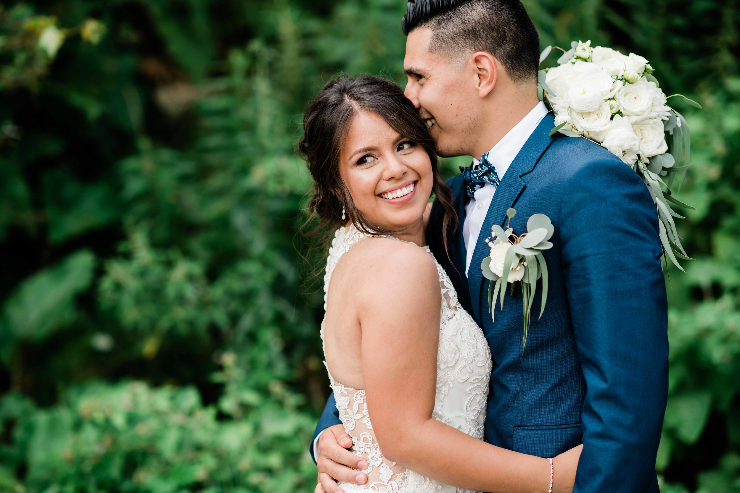 Groom kisses bride's head as she smiles
