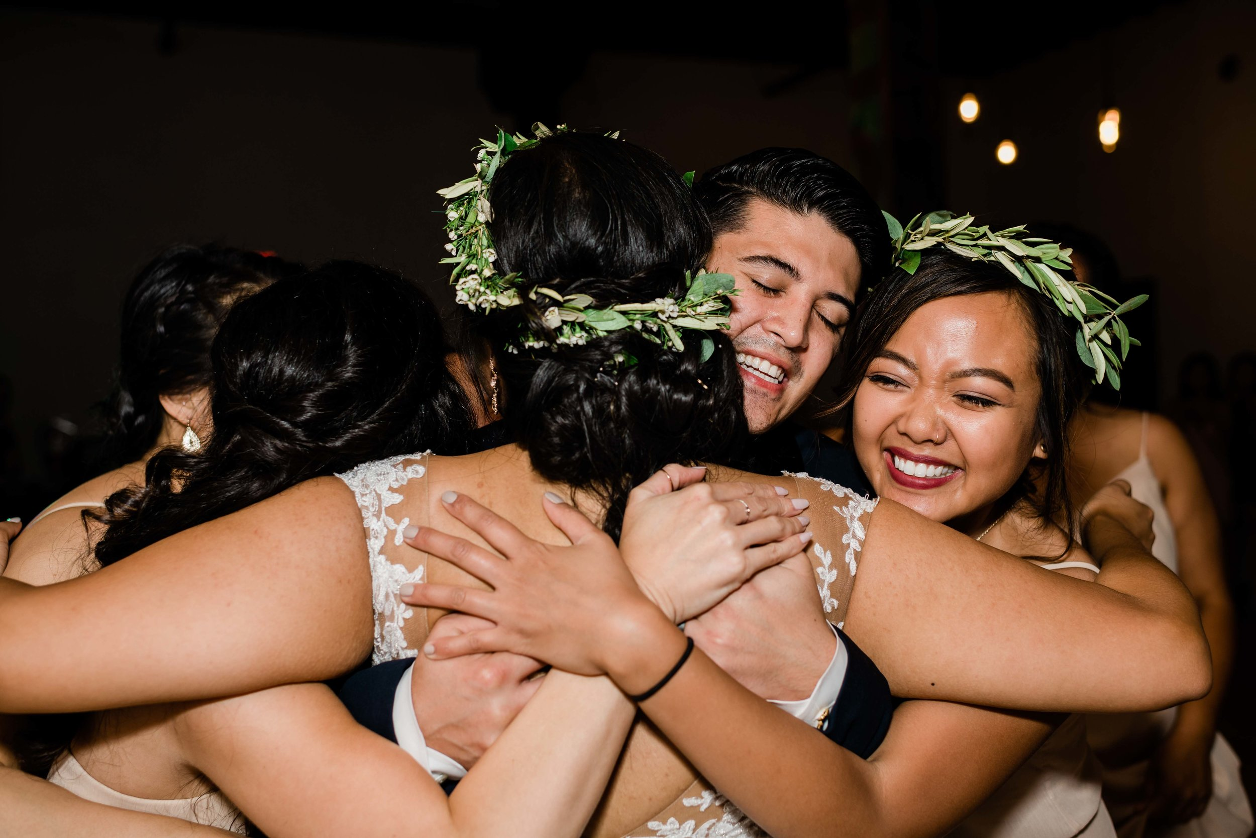 Groom hugs bridesmaids