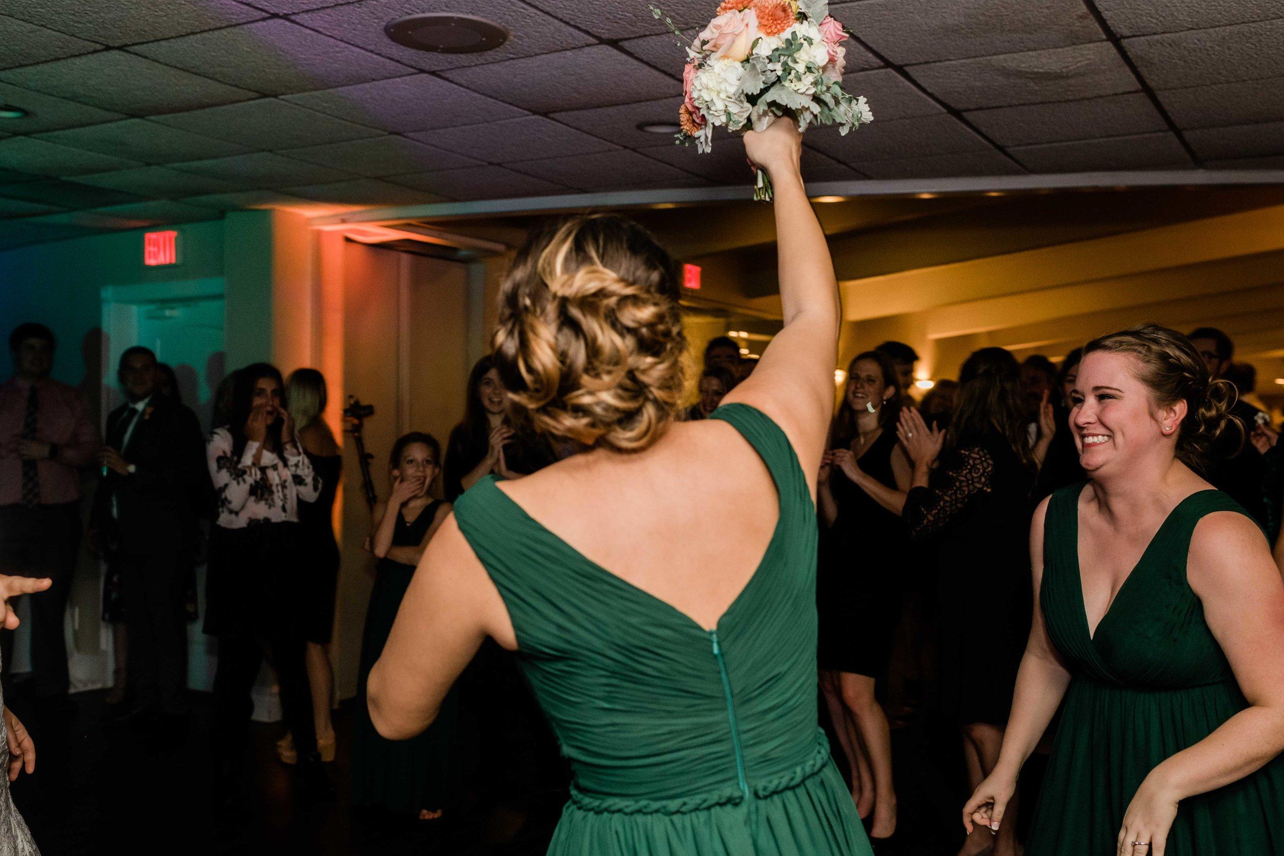 Bridesmaid catches bouquet during bouquet toss