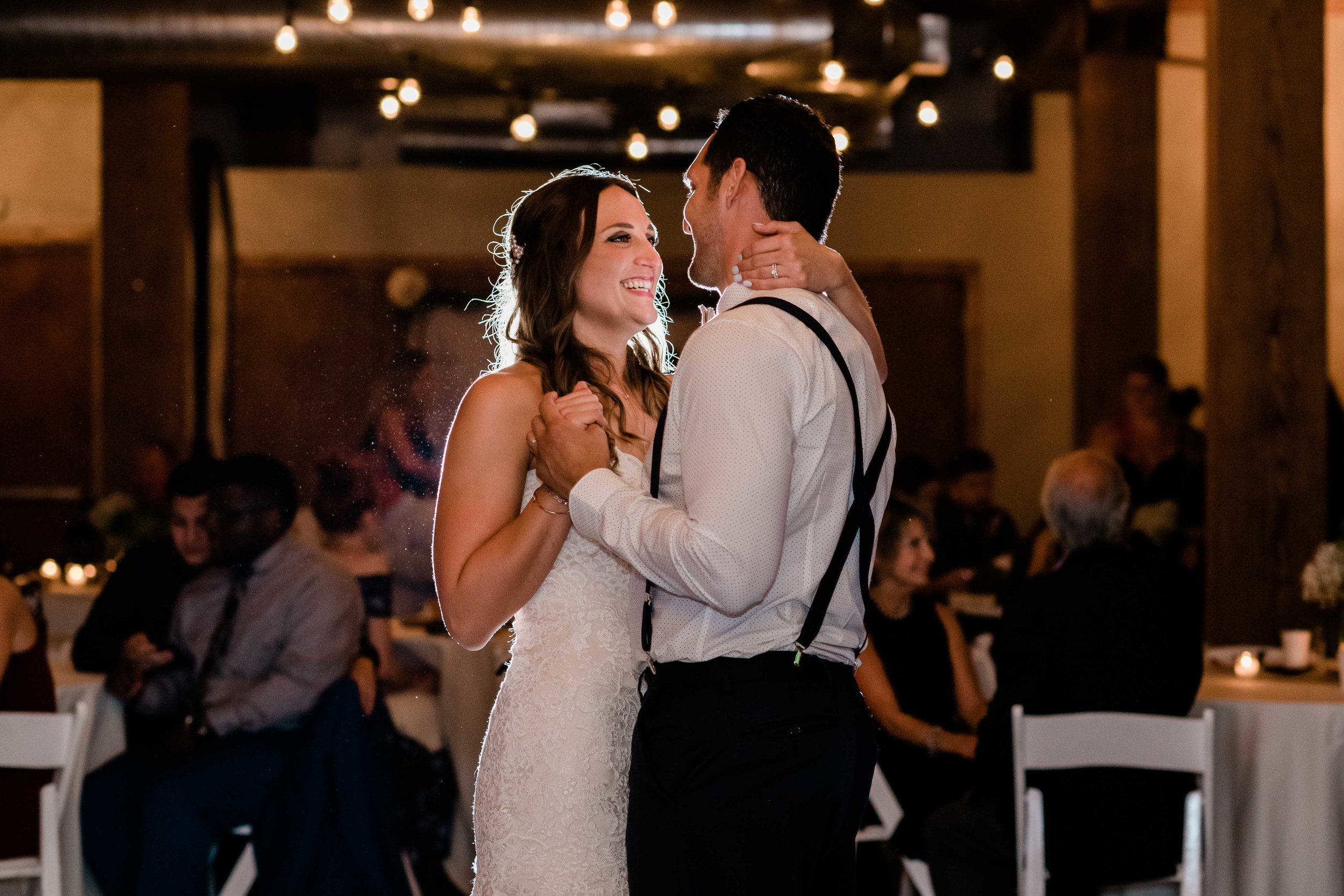 Bride smiles at groom during their first dance