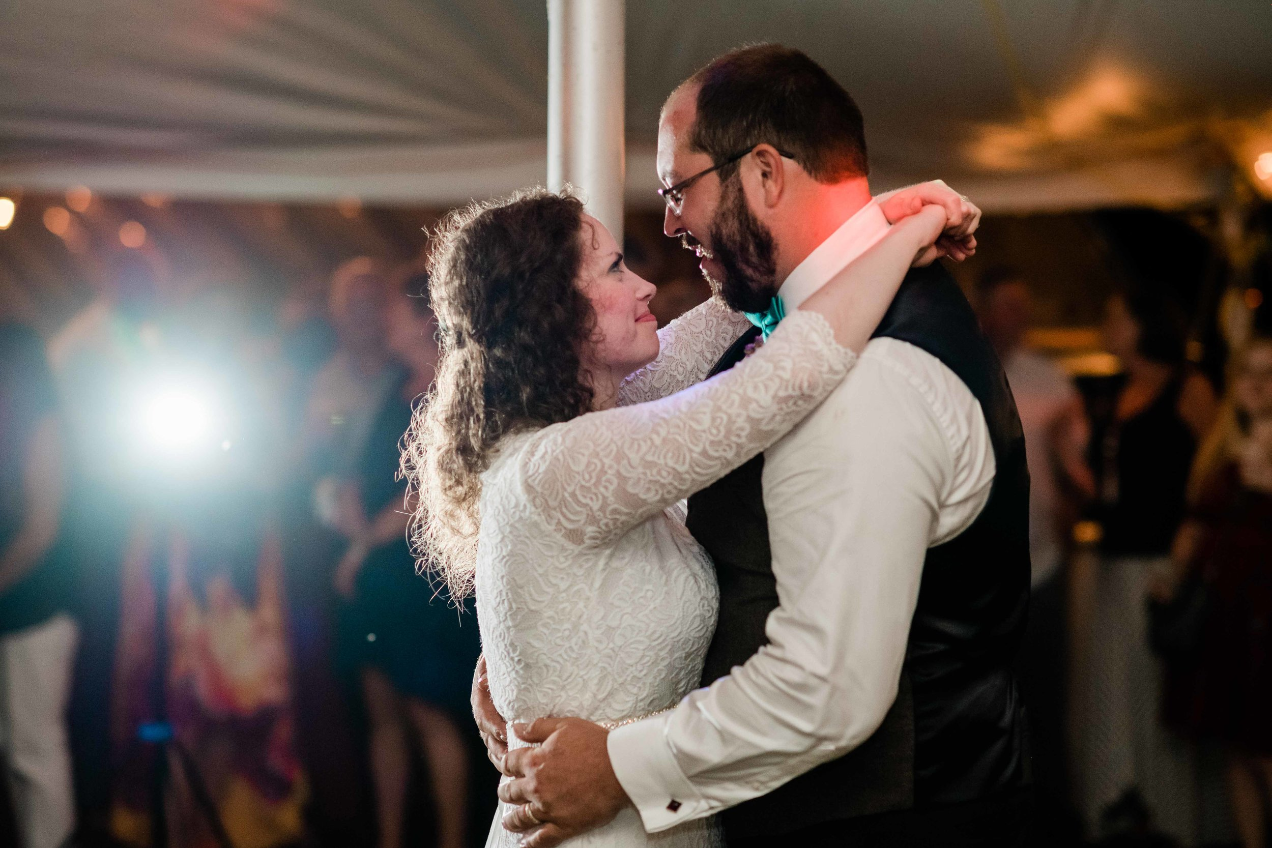Bride and groom look into each other's eyes during first dance