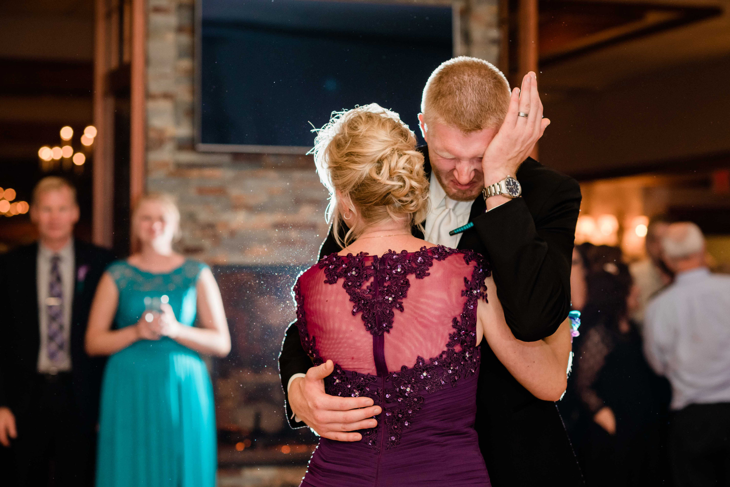Groom wipe away tears as he dances with his mom