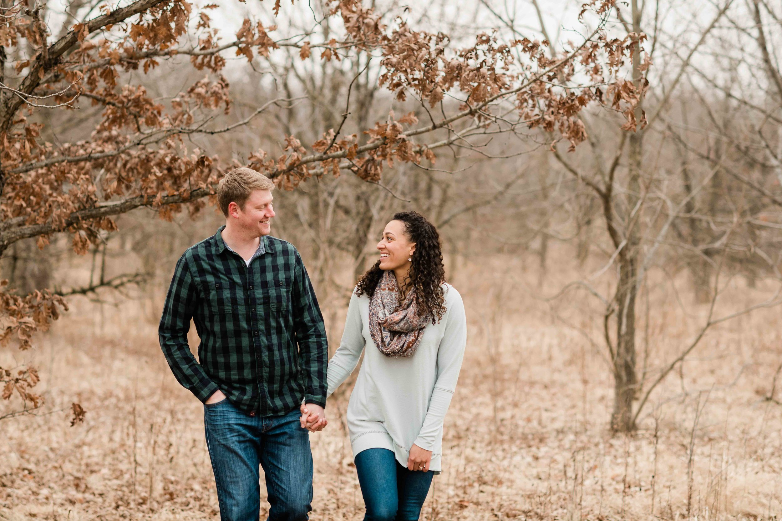 Engaged couple walking in a field before winter